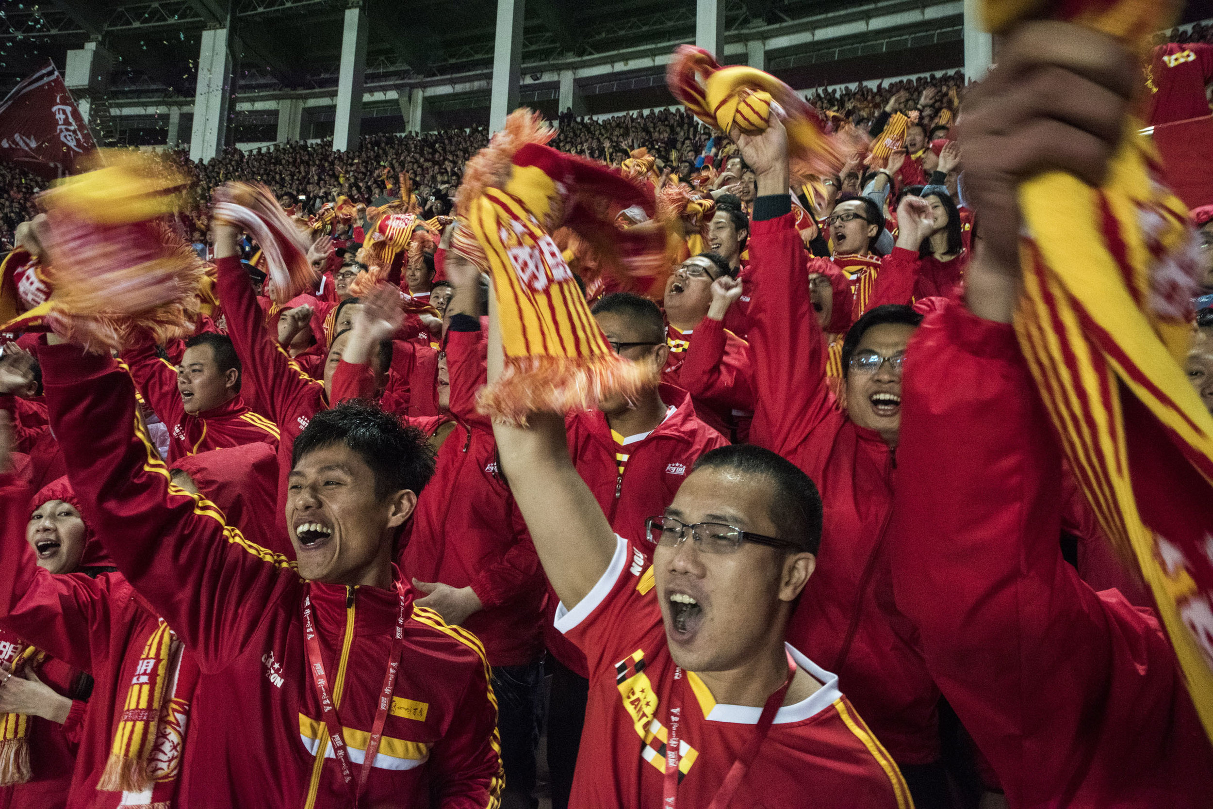 At The Guangzhou Tianhe stadium Evergrande supporters cheering as their team just scored a goal during a Chinese League game against Changcun Yatai F.C..