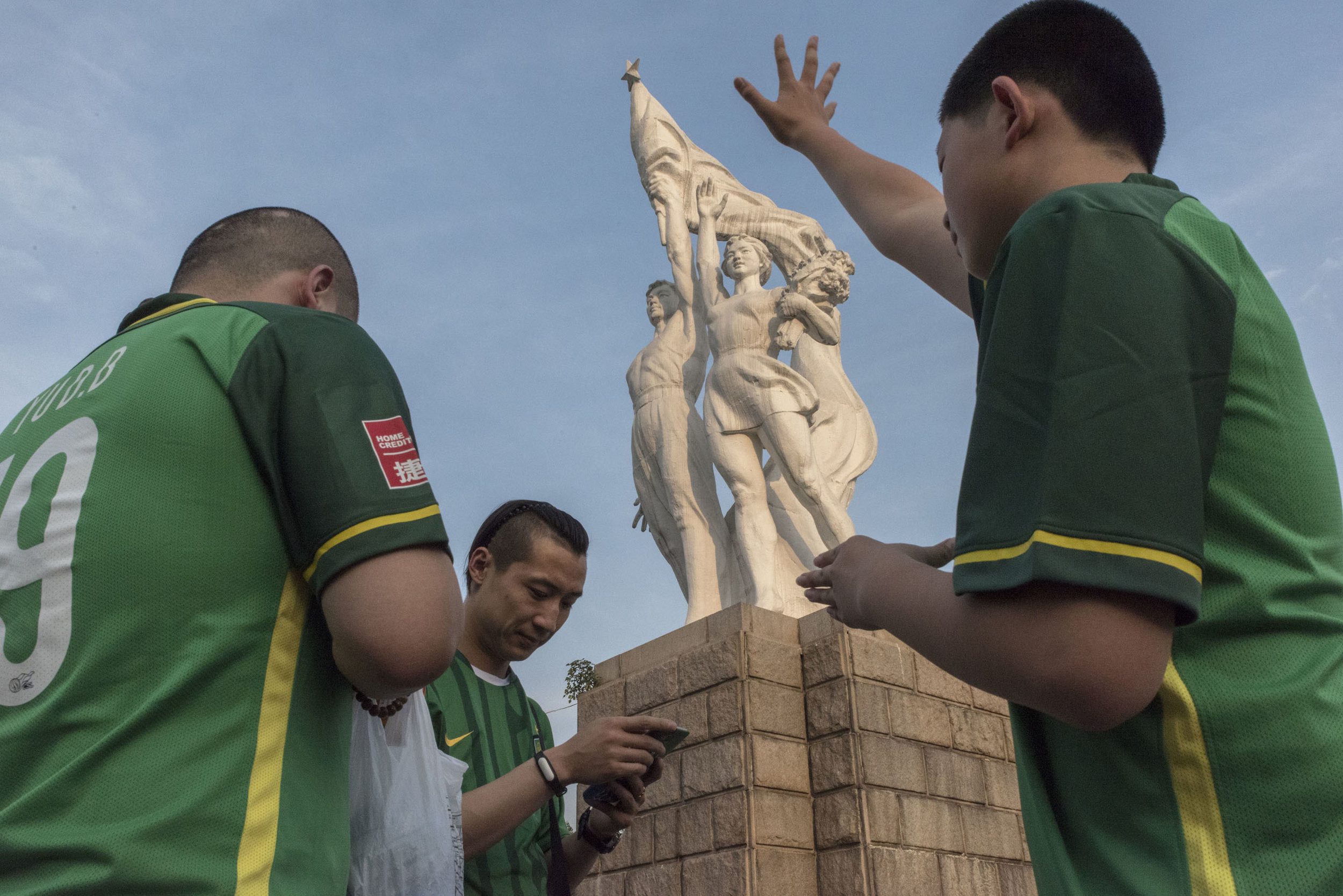 Outside the Workers stadium in Beijing, supporters of the Beijing club Guoan waiting for friends by a statue representing workers.