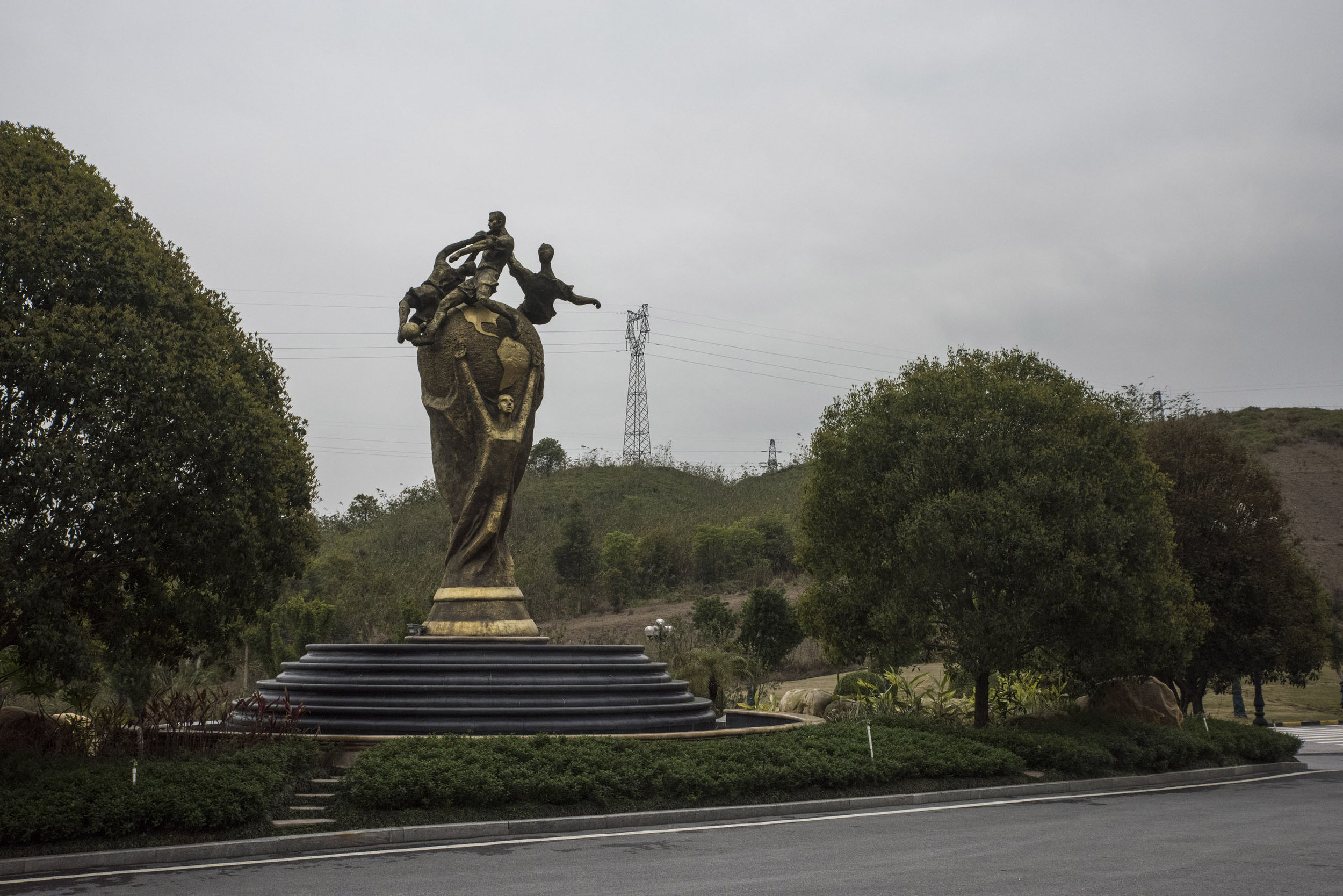 A giant model of the World Cup trophy outside the Evergrande Football school in Guangdong.  The school, the biggest in the world with hundreds of students and dozens of football fields has become a symbol of China's efforts to become a world class football nation.  Since this photo was taken the school had to remove the statue at the FIFA's request.