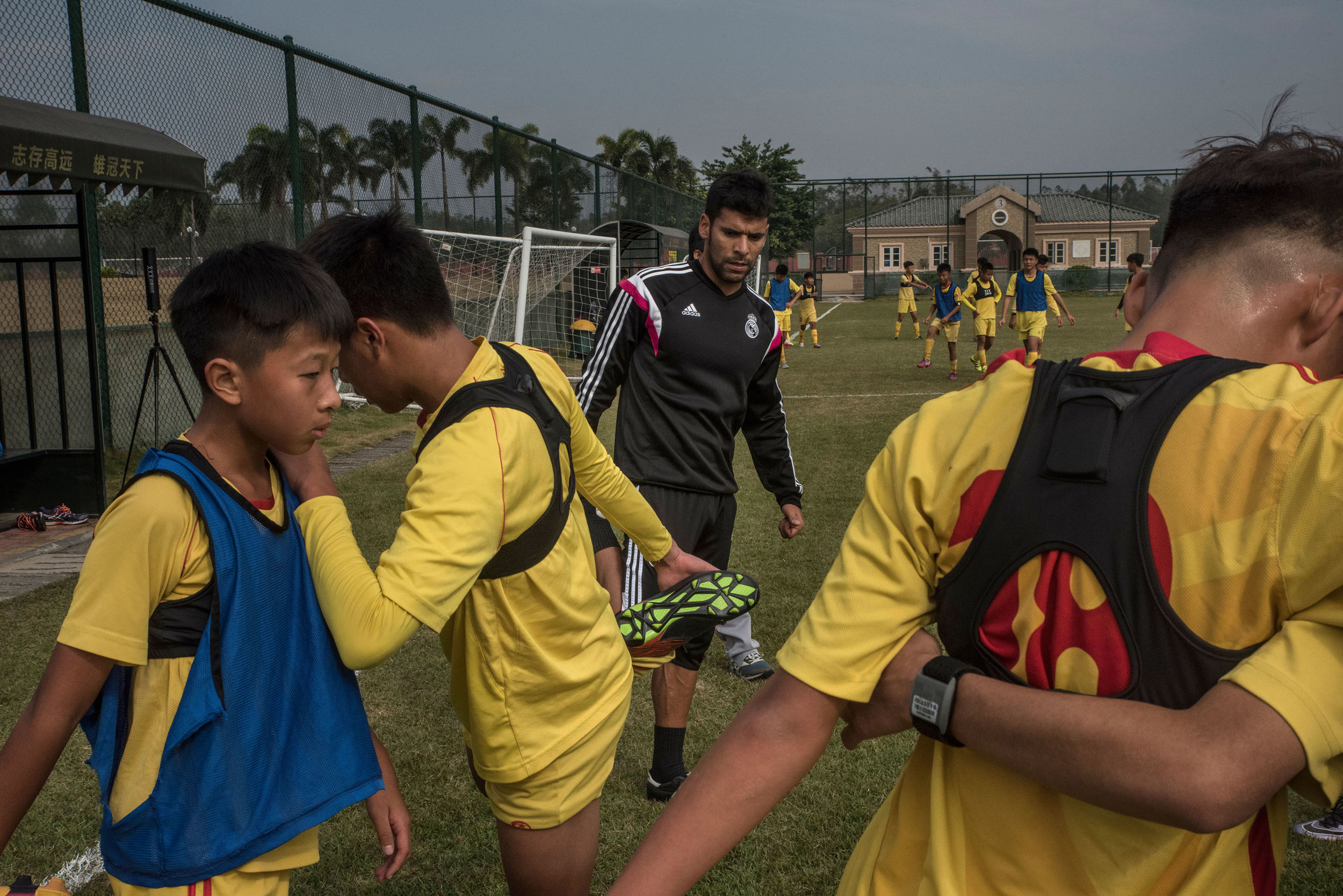 Students of the Evergrande football school doing stretching exercises under the eyes of a spanish coach. The school football training has been set up in partnership with the Real Madrid and number of Spanish coach work there.
