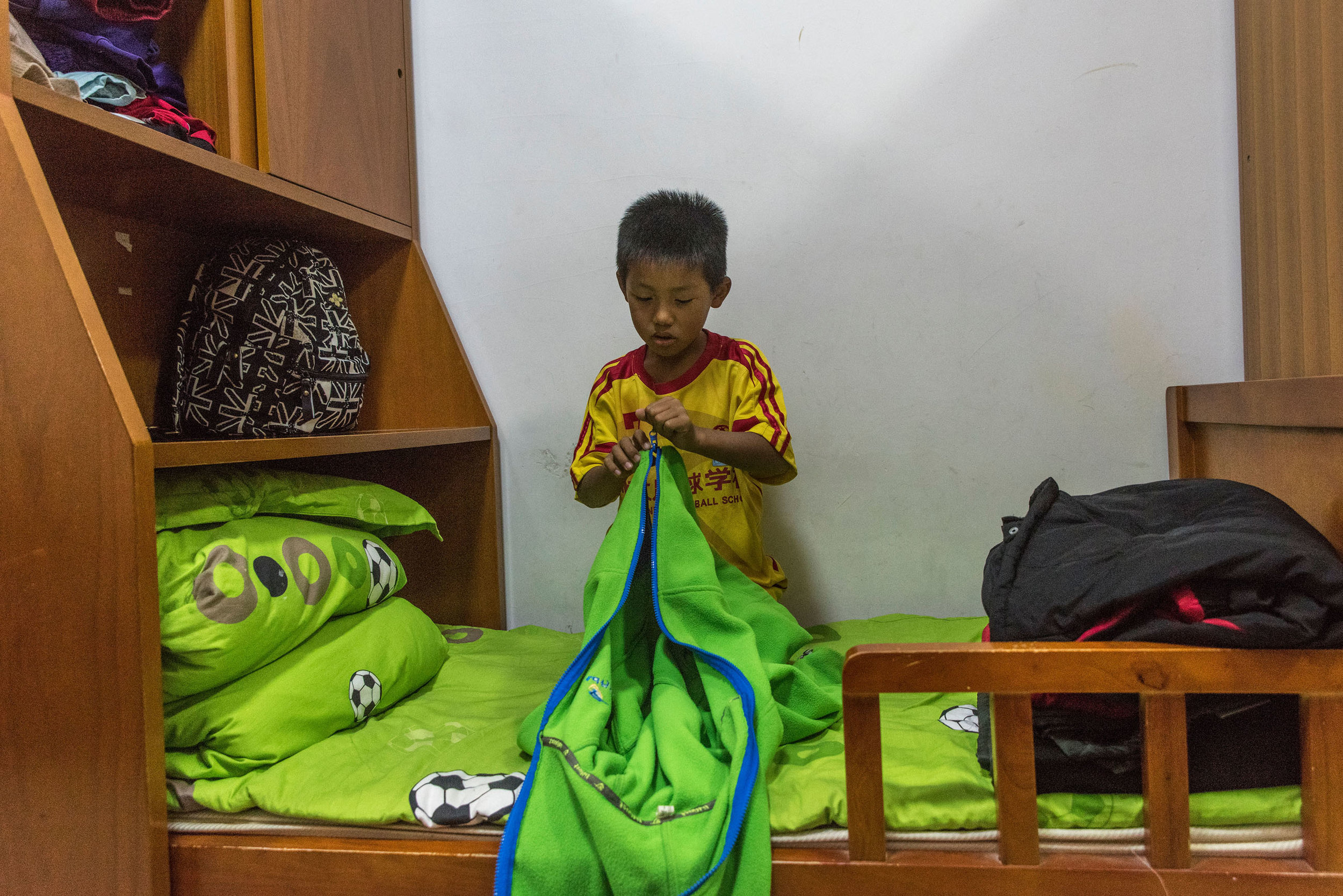 A 9 years old student preparing his bed for the night at Evergrande Football school.
