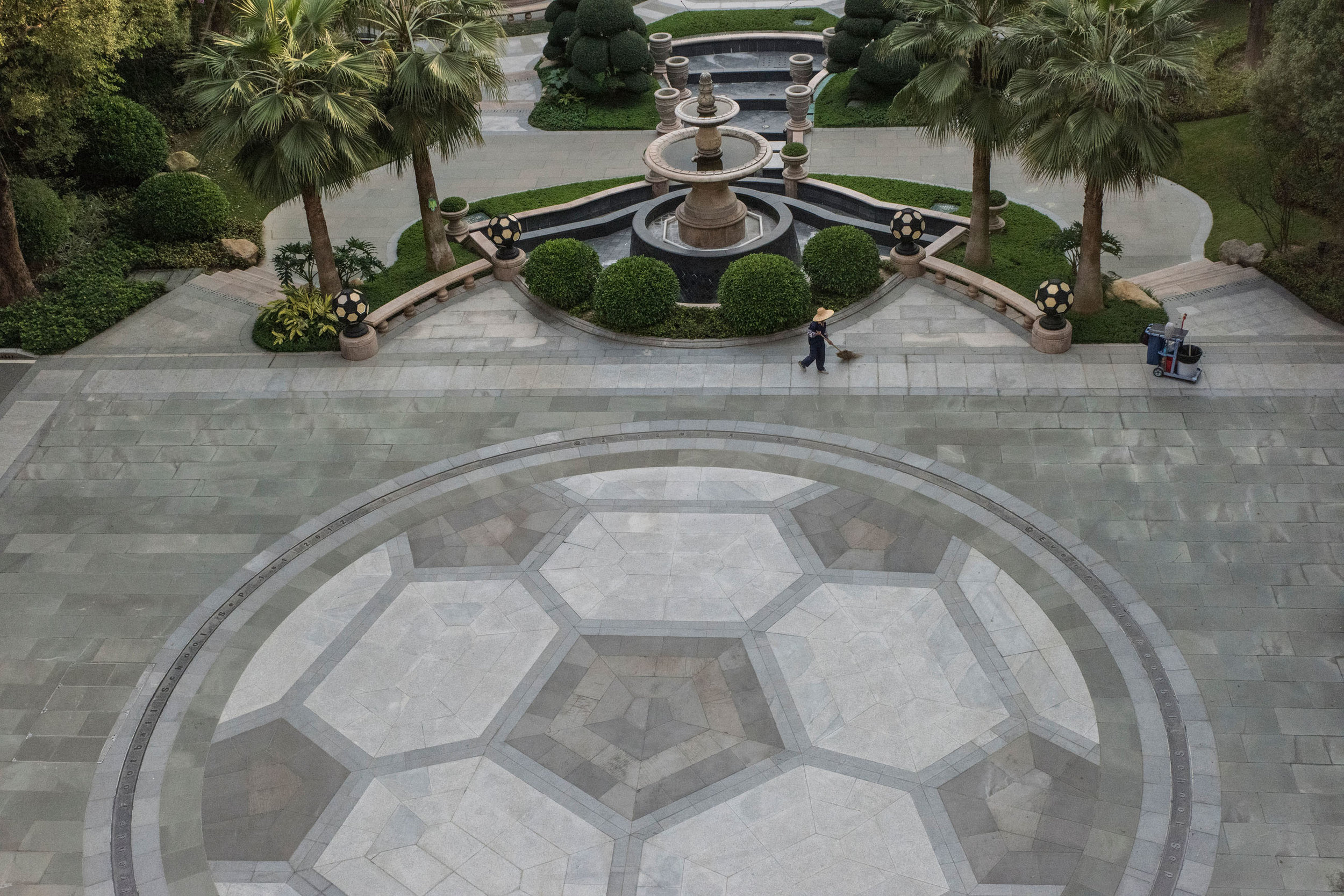 An employee sweeping the alleys of the Evergrande Football School manicured gardens where a mosaic represents a giant soccer ball.