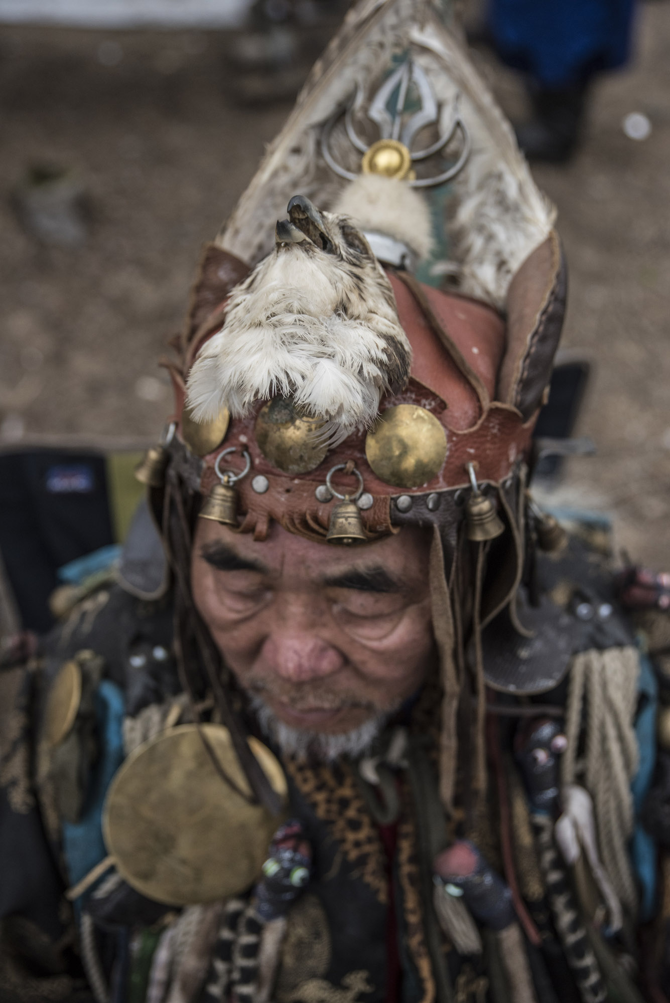 A shaman wearing a hat adorned with an eagle head.   In the shamanist belief, animals have souls and they reincarnate themselves.