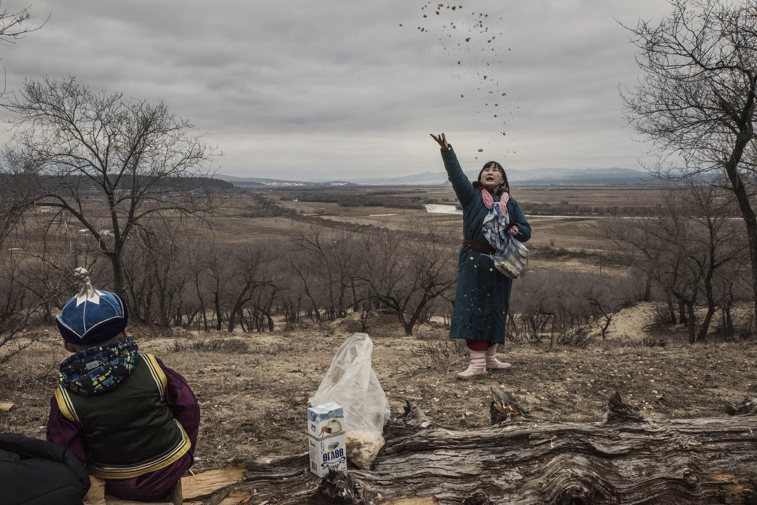 A woman throwing bits of cake to the sky, as an offering to Tenger, the main spirit of shamanic practices.     At the heart, shamanism is a worship of nature and the spirits that rule mountains, rivers and the sky.