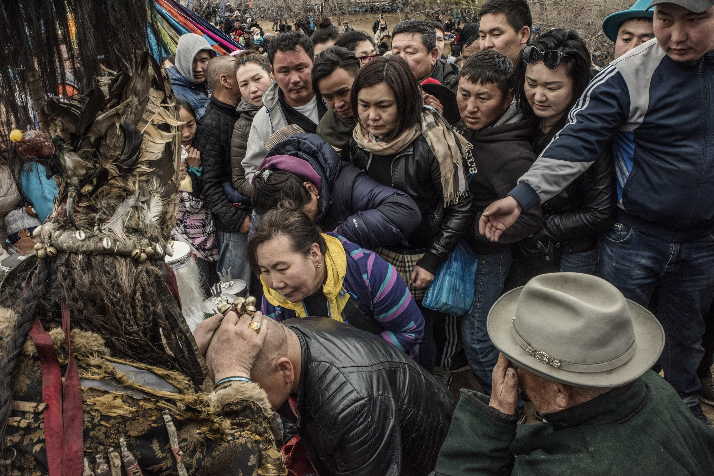 Pilgrims lining up in front of a shaman, master of ceremony at a celebration of spring, waiting to be blessed. Shamans work as mediators between the spirits and human beings and are believed to hold powers such as healing.