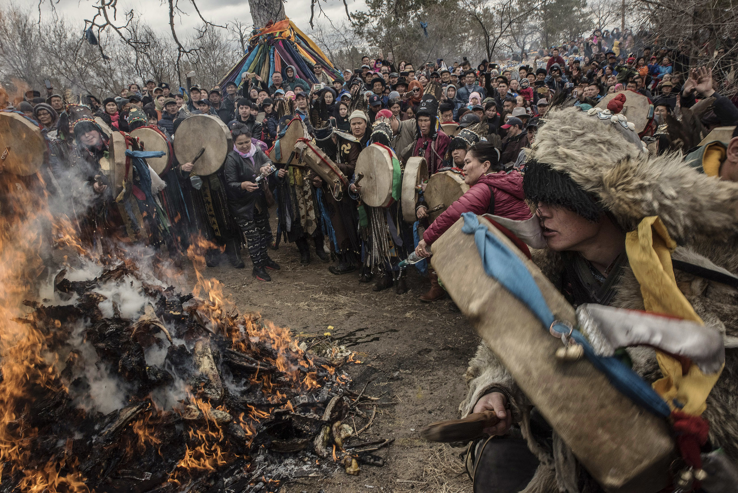 "Near the ""mother tree"", a shaman dressed with wolf skins, is getting into a trance, connecting with his spirit, as fellow shamans beat their drum. Pilgrims have fed the fire with lamb ribs wrapped in  a green khata enclosing handwritten notes of their wishes."