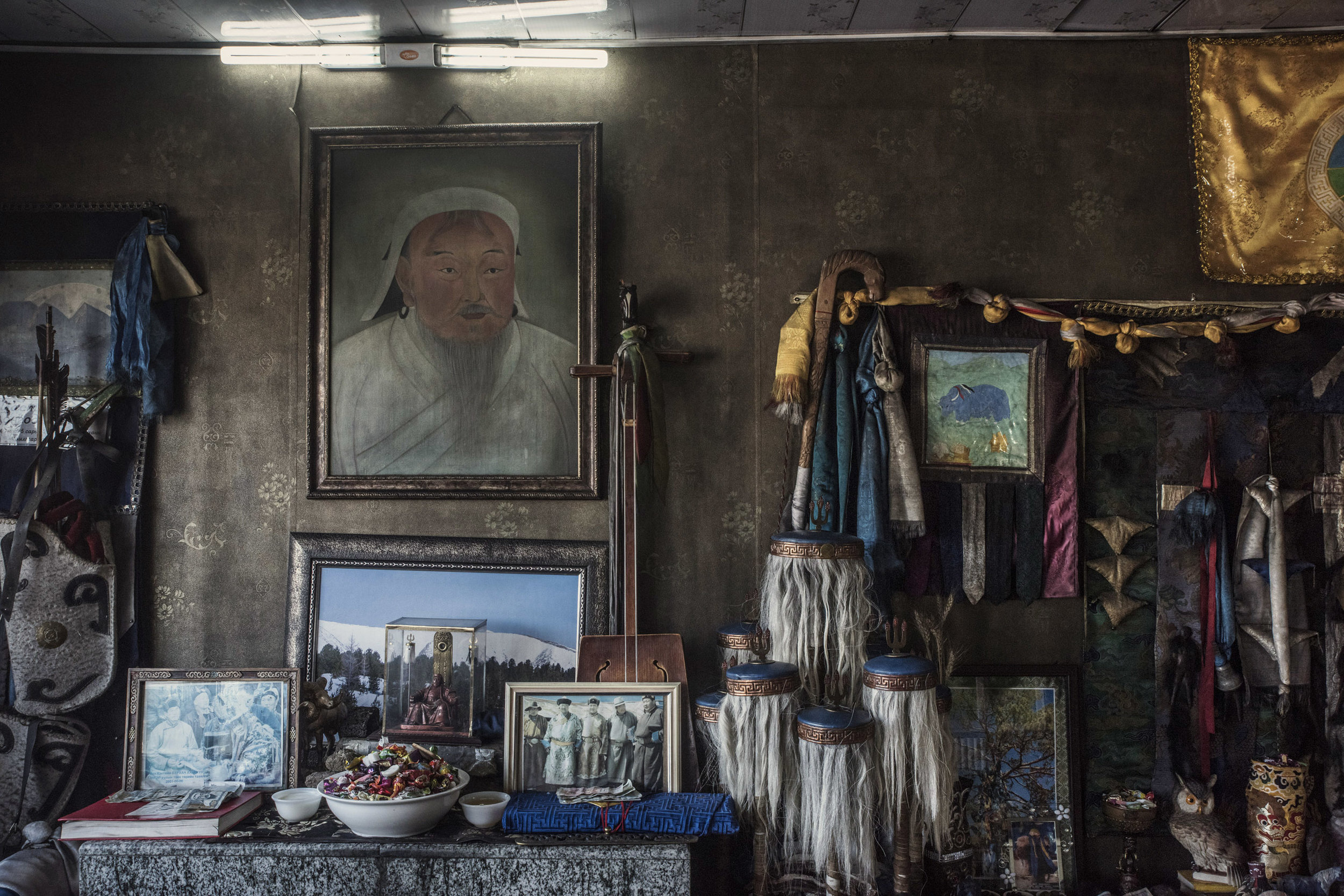 An altar in the prayer room of master shaman Byambadorj with a portrait of Genghis Khan on the wall. At the right of the altar stands a frame picture of Byambadorj with former Mongolia president Nambar Enkhbayar (3rd from left) and Badmaanyambuu Bat-Erdene (first from right) Mongolia former National wrestling champion and current parliament member. With Shamanism increasing popularity in Mongolia, it mixes with politics: many members of parliaments practice shamanism, and even some being shaman themselves.   Genghis Khan portraits are ubiquitous in Mongolian homes including  Shamans' practice rooms. The cult of the Mongolian ruler is part of local shamanist belief. Genghis Khan practiced shamanism himself and he is considered the master of all shamans. His spirit is frequently called upon during shamanic ceremonies.