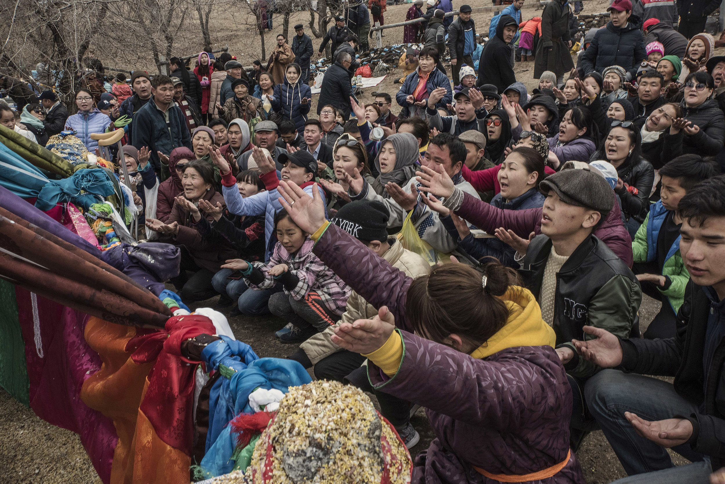 "Pilgrims who have come to attend a shamanic celebration of spring in northern Mongolia, kneeling palms open to the sky in front of the ""mother tree"" a symbol of eternity believed to have special powers."