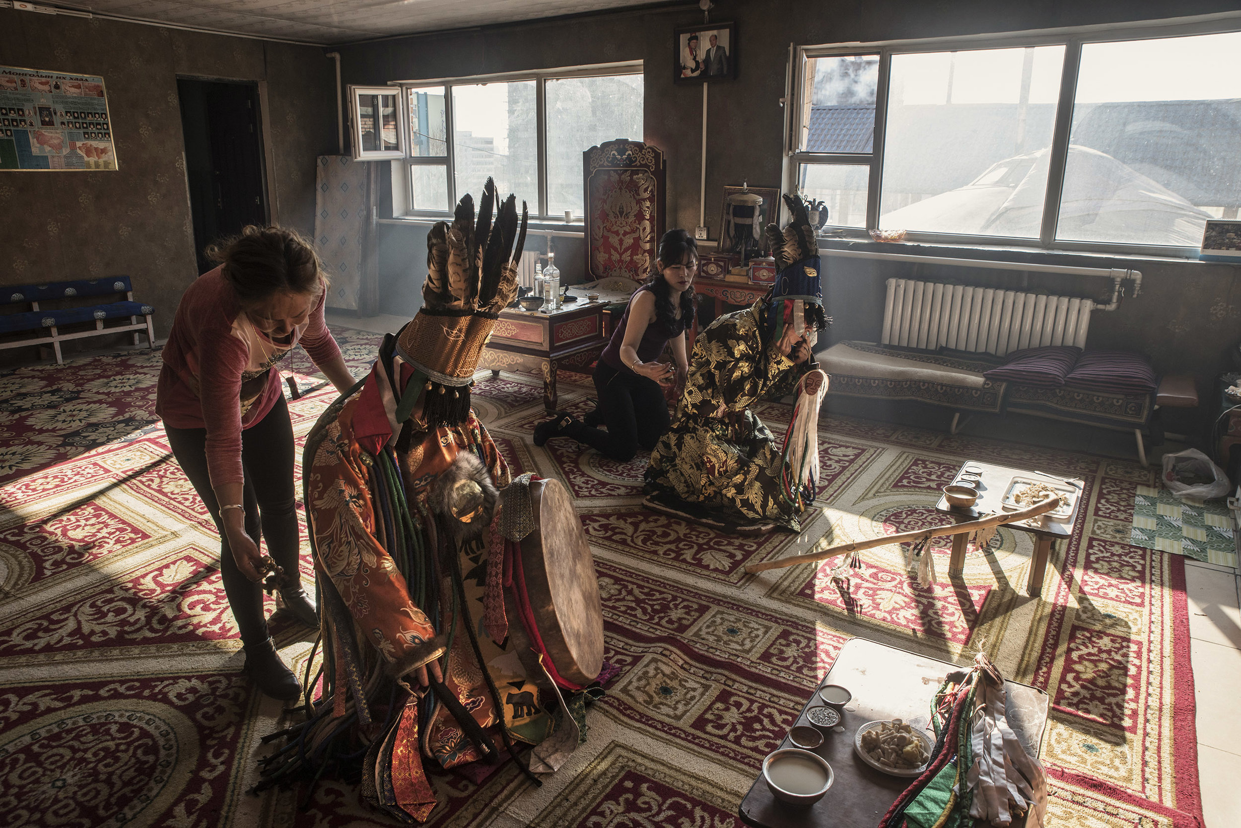 Suhe and Tugsuu, ethnic Mongols from China preparing to get in a trance at the home of master shaman Byambadorj under the guidance of his daughter Enkhoyun (left). Tugsuu and Suhe have come to Ulaanbaatar to be initiated as shamans.   The call to become shaman usually occurs during a prolonged illness, during which a connection with a spirit happens. The apprentice then seek the help of a master shaman to learn the skills that will allow them to get in trance and connect with their spirit on a regular basis. The training of novice shamans is good source of incomes for master shamans.