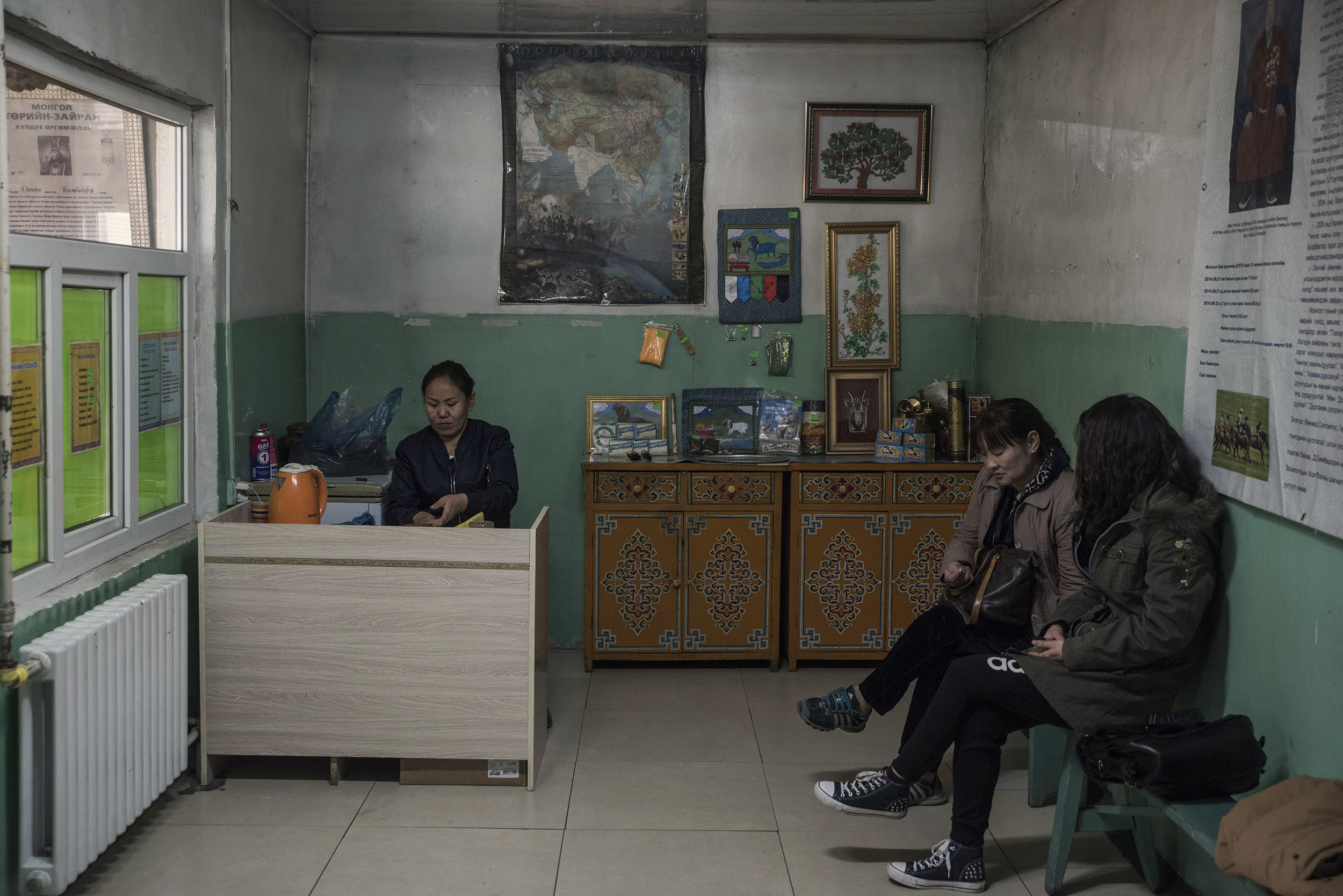 Two women in the waiting room of Byambadorj's home, waiting  for an audience with the master shaman. Across from them a menu of the shaman services has been posted on the wall : from curing health problems, to removing or casting curses, including fortune telling.   Behind the receptionist, a large poster shows the boundaries of the Mongolian empire at the time of Genghis Khan. The revival of shamanism coincides with a rise of nationalism. Shamanism is closely associated with the Mongolian identity and culture.