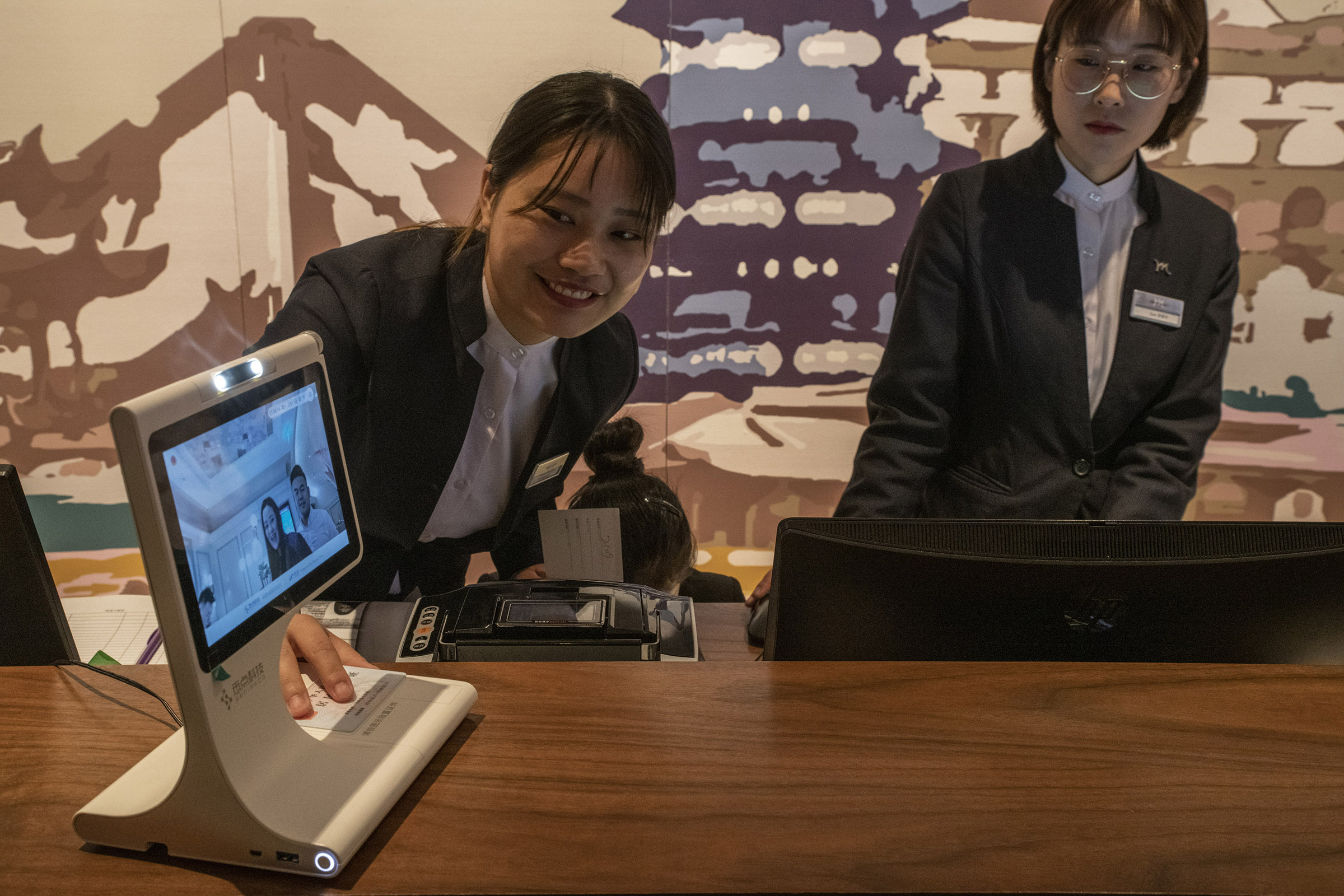 Receptionists at a hotel in Hangzhou are scanning the ID of guests checking in. The scanner equipped with a camera and a facial recognition software is ensuring that the guests are who they claim to be.