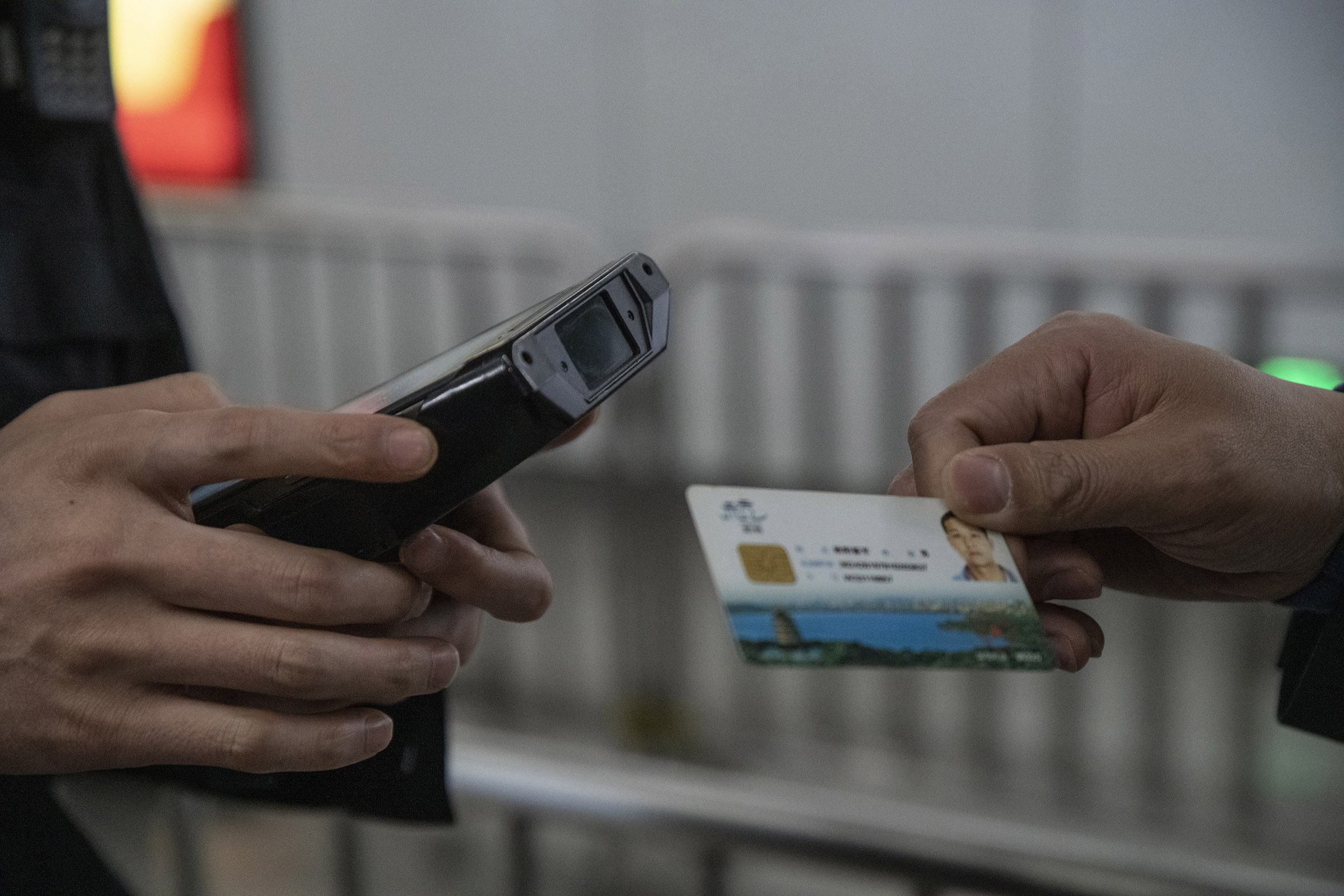 At a security checkpoint in Hangzhou, a pedestrian is handing his city smart ID card to a policeman equipped with a scanner. The card featuring a microchip, contains a large amount of private data allowing him to use city services (health, education,social security funds  transport..etc) and bill payments. The card is also used for a city wide voluntary social credit rating system which so far has few users.