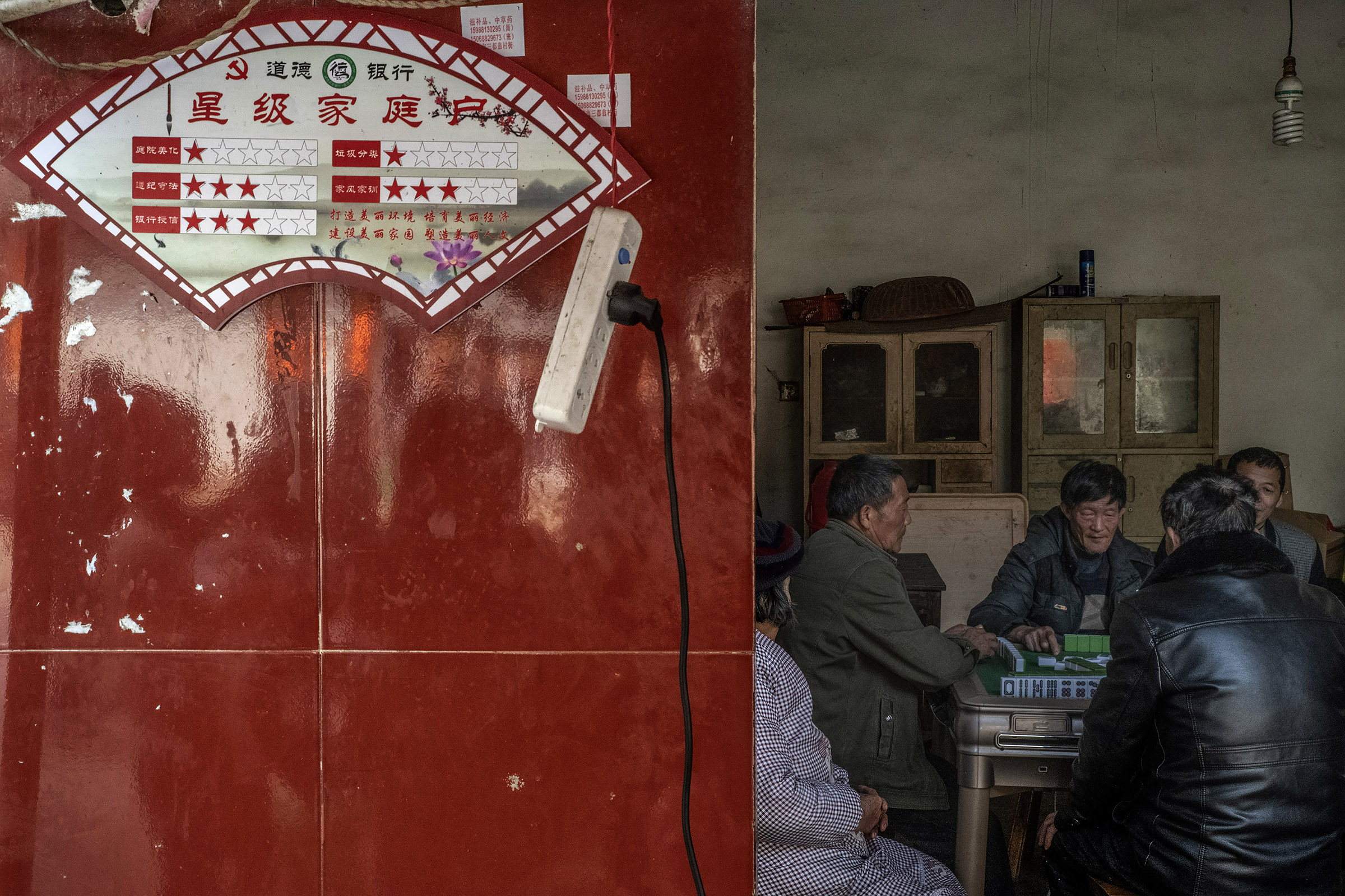 In Yangqiao (Zhejiang) locals are playing Mah-Jong in a home where the household social credit score is displayed on the wall. The social credit system implemented in this village since 2018 is based on five criteria : cleanness and tidiness of courtyard, Observance of laws and regulations, bank credit, recycling, family values. Locals describe the system as useless and of no effect on their daily behaviour (which includes for many, gambling). However, this local experience has been hailed as a success by local and national State media and will be extended to other villages and towns in the region.     Chinese authorities have announced their wish to have a nationwide social credit system in place by 2020. However the details and feasibility of such a system are yet unclear.