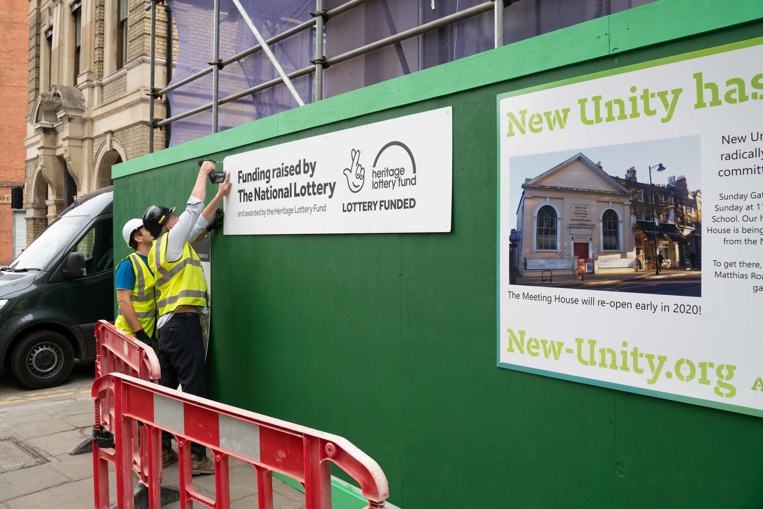 The building team mounting signage on the recently erected green hoarding facing Newington Green