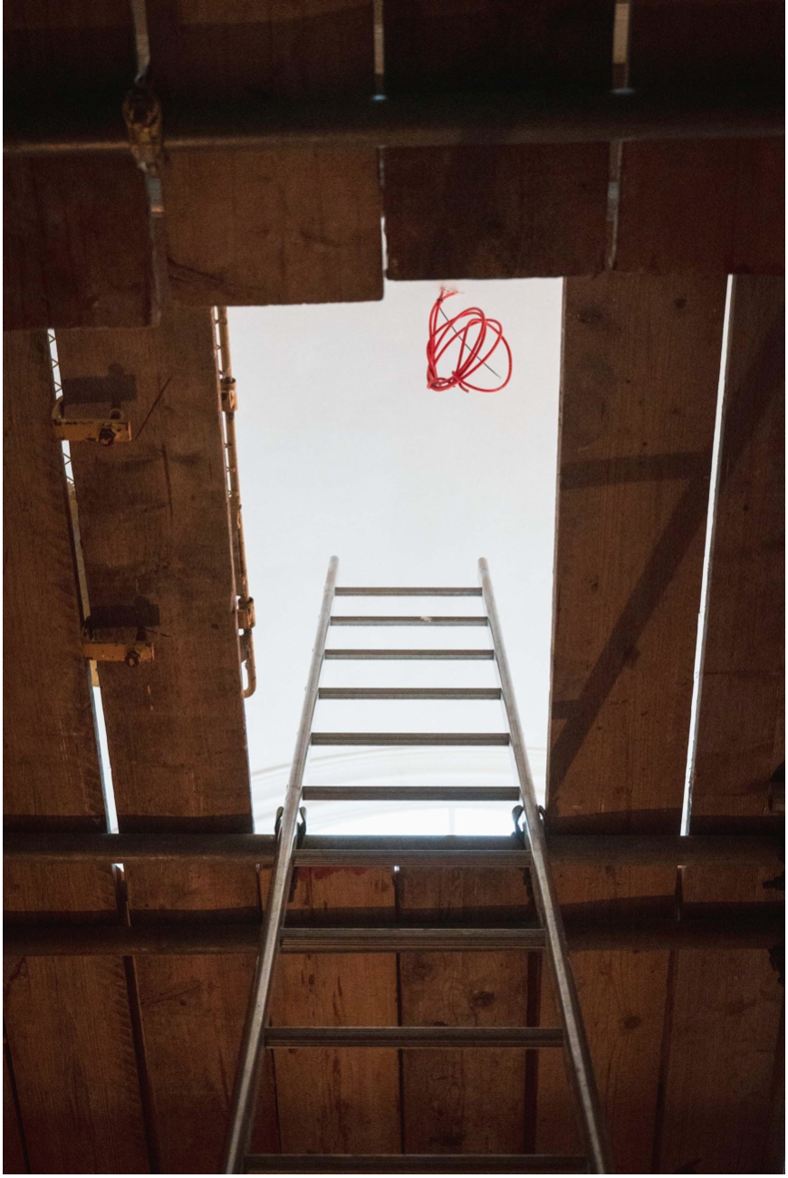 """Ladders lead to the top level of the """"birdcage"""" scaffold and beyond that the brilliant white of the renovated ceiling of the Meeting House."""