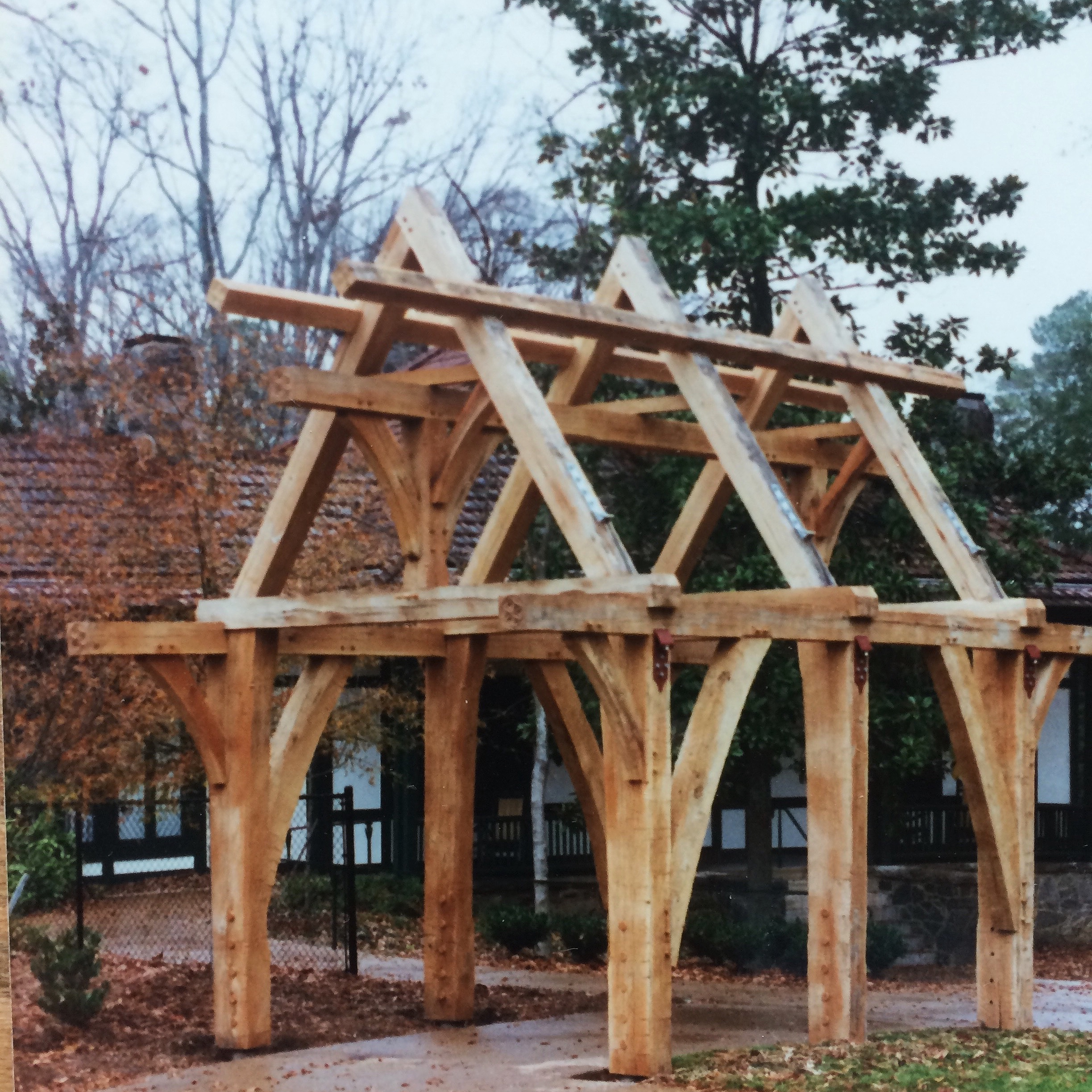 In 1994-1995, I worked with the construction of two timber-framed oak pavilions for St. Philip's Episcopal Cathedral in Atlanta, accessory structures to the rectory (the building in the background) and the parking area. Officially, my role was as a woodcarver, adding details to the framing members which had been cut and fitted before I arrived. Later, I helped with raising and completing the structures. [The lych-gate is a common feature in the English landscape, the separation between the church and the churchyard (or cemetery). Traditionally, a body was laid out in the lych-gate prior to interment.]