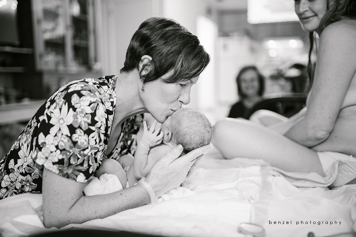 Midwife kisses baby