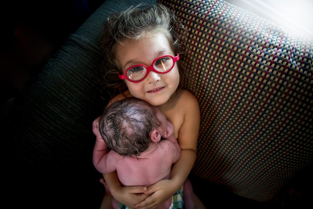"""""""A Sister's Warmth"""" - by  Nicole Lahey  This image was one of my most favorite shots from the contest, and it also happened to be one of Monet's favorites as well. We both just love big sister's connection with the camera, her glasses and of course that perfectly pink baby brother. I can't stop looking at it!"""