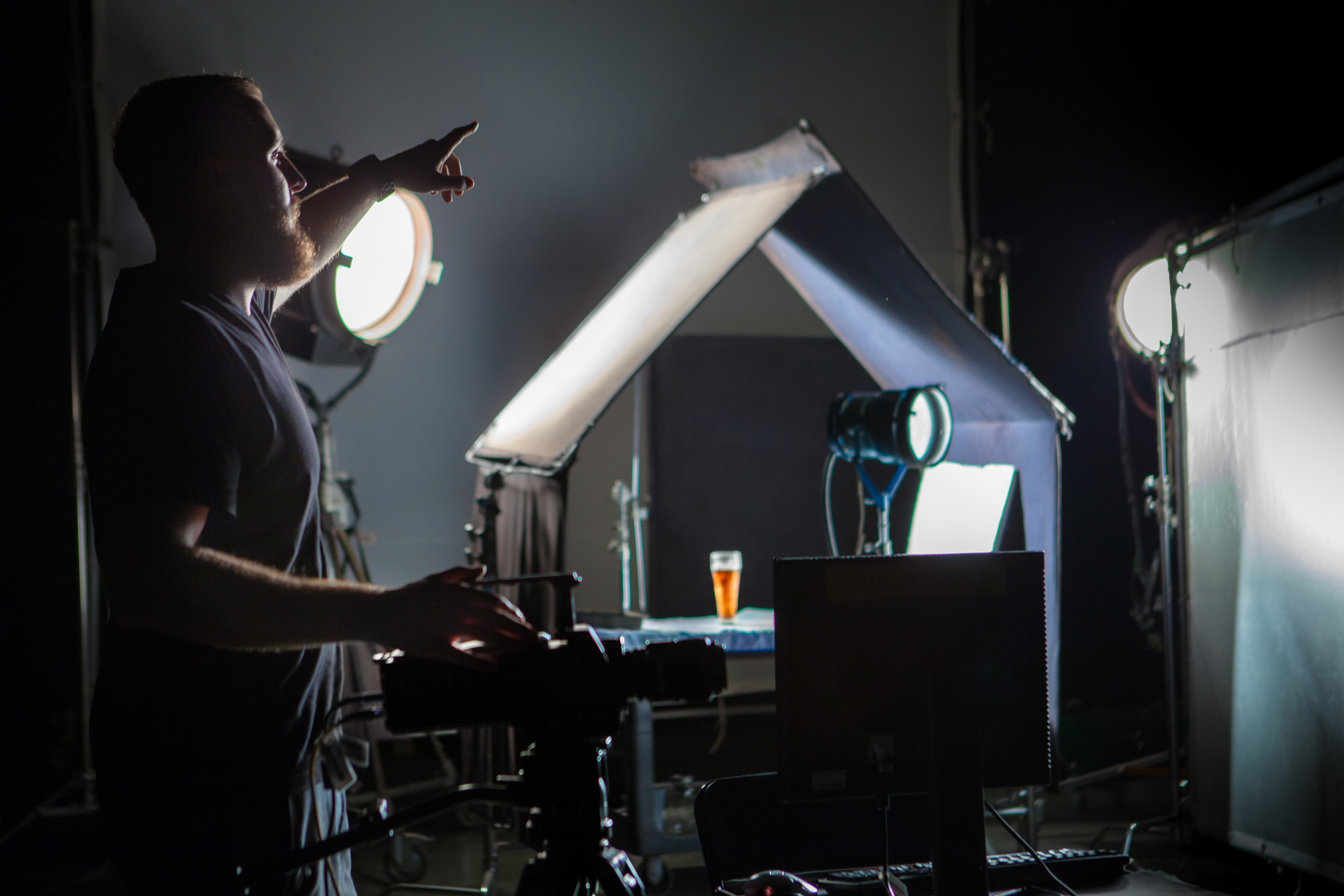 MAKINGTHAT BEER SPARKLE!   Our Production Manager, Dave Lion, getting his lights set.  In order to s  hoot  up to 1200 frames per second, an abundance of light is needed to compensate for the high frame rate.  Here we have two 10-thousand watt fernels andan open-face 2K,all to light one glass of beer onthe Phantom camera. Sometimes bigger really is better. Try replicating these shots on youriPhone!