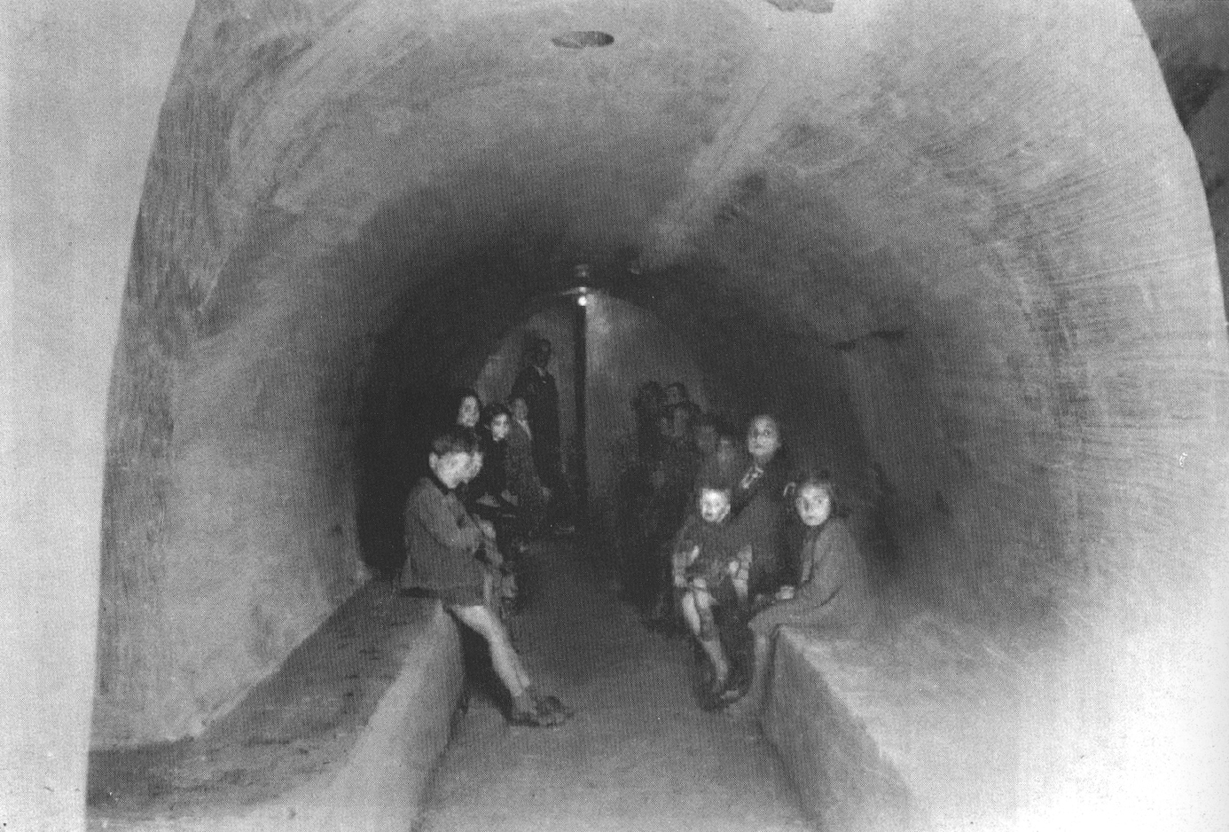 Families huddle in a bomb shelter under Naples during World War II.  Image Credit: Photographic History of Naples, edited by Gloria Chianese, published by Intra Moenia