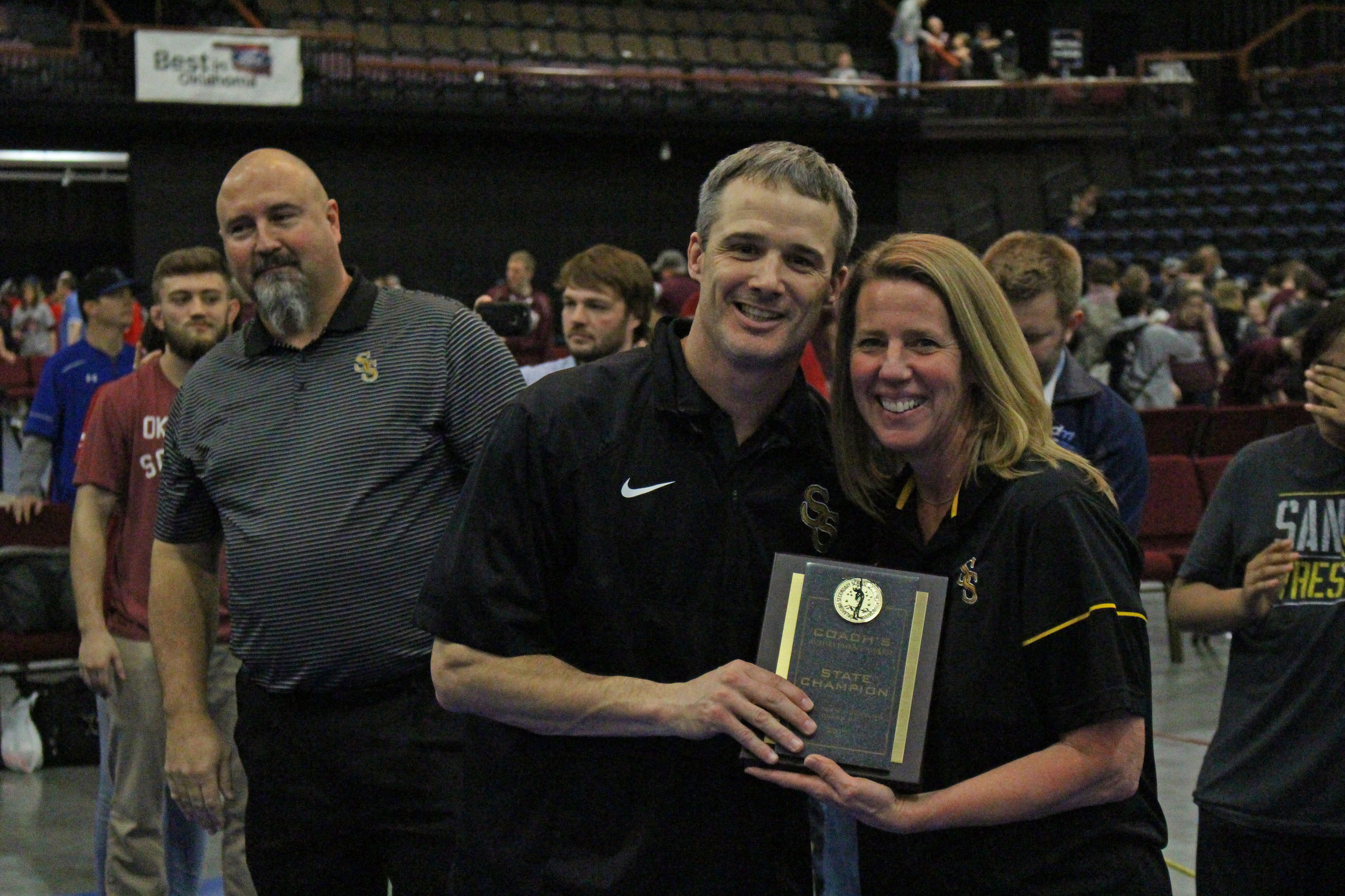 Head Coach Kelly Smith is presented with the Coach's State Championship plaque by Sand Springs Superintendent Sherry Durkee.