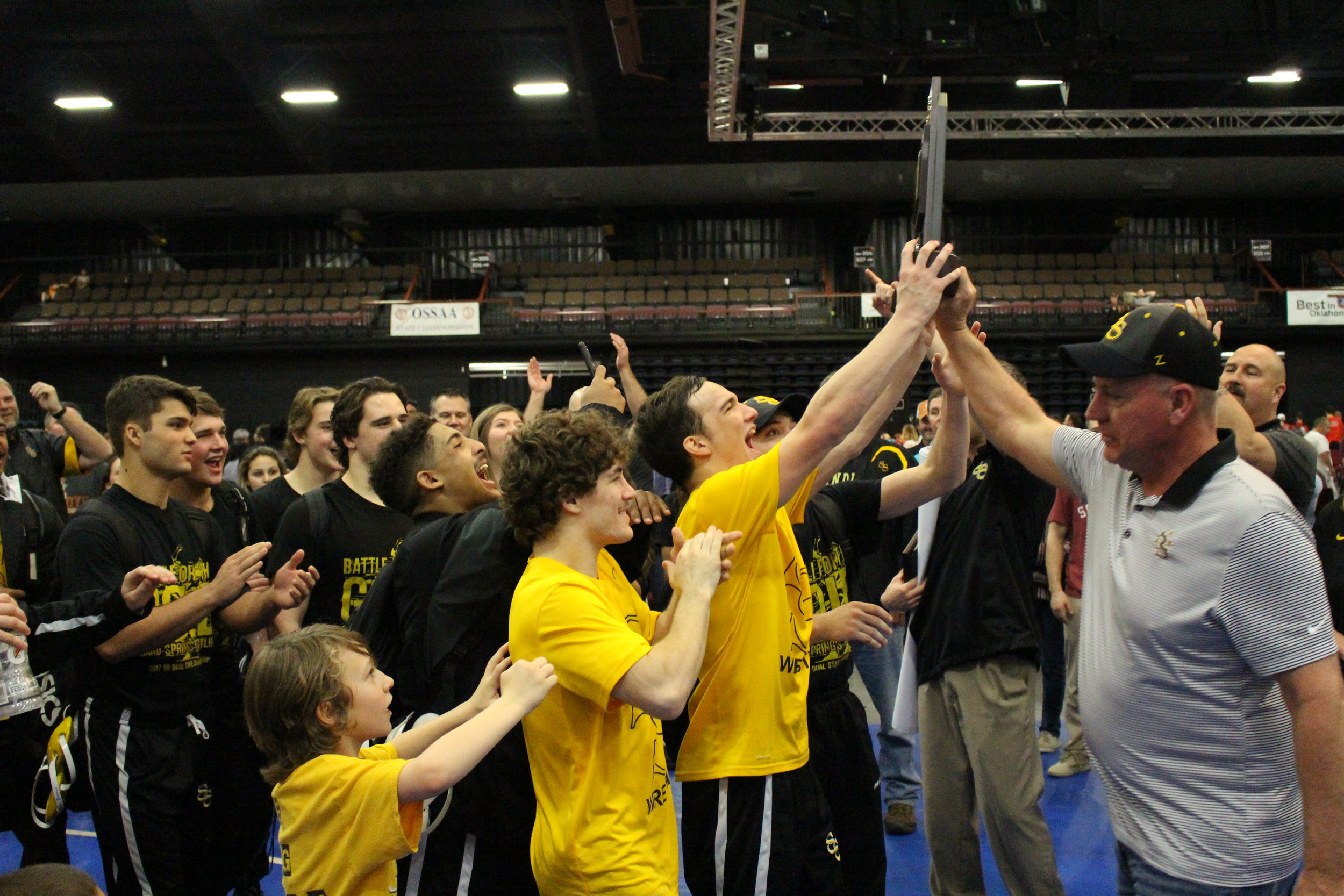 Charles Page High School Principal Stan Trout presents the Sandites with their Dual State Championship trophy.