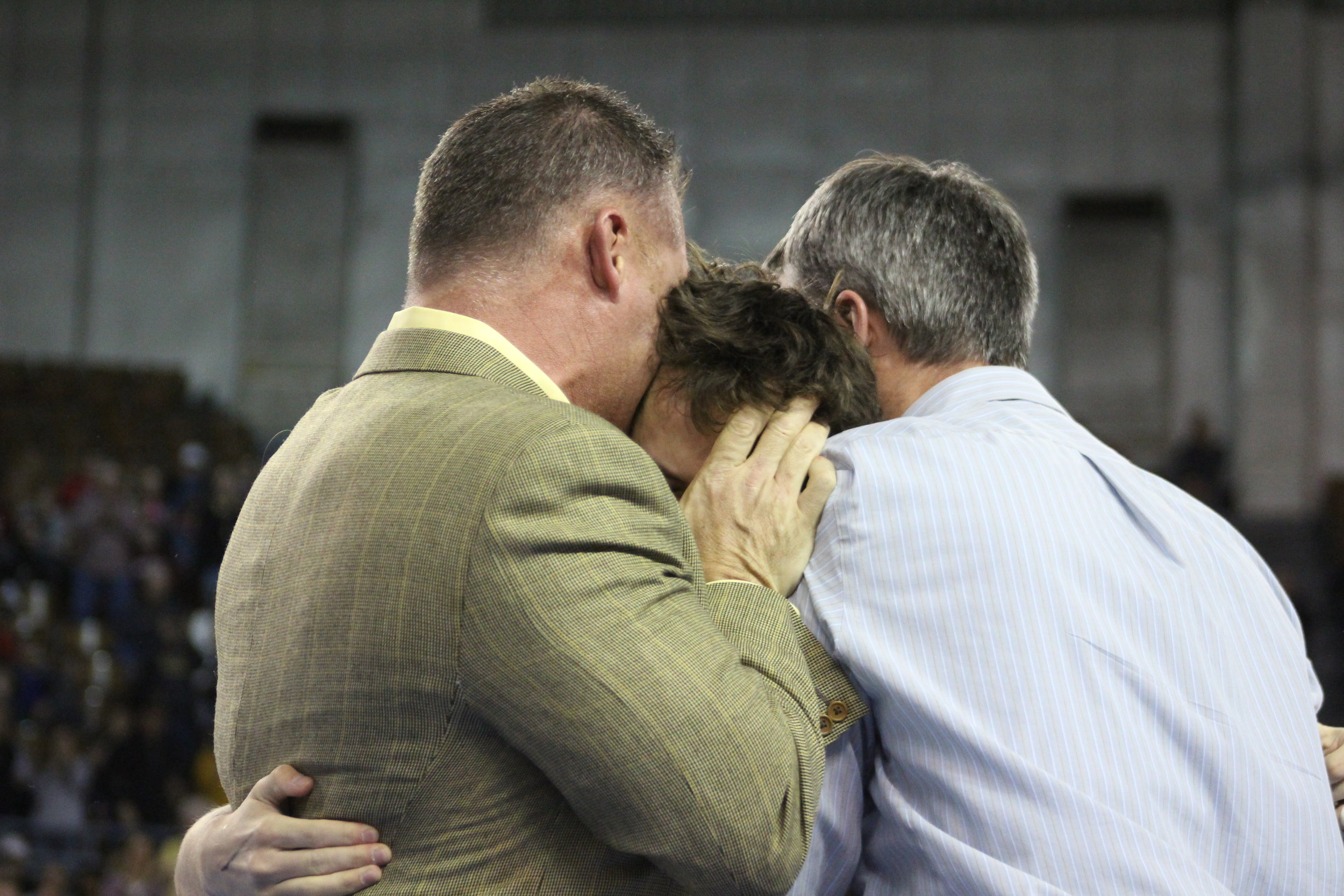 Coaches Kelly Smith and Derek Fix hug Riley Weir in celebration of his first State Championship.