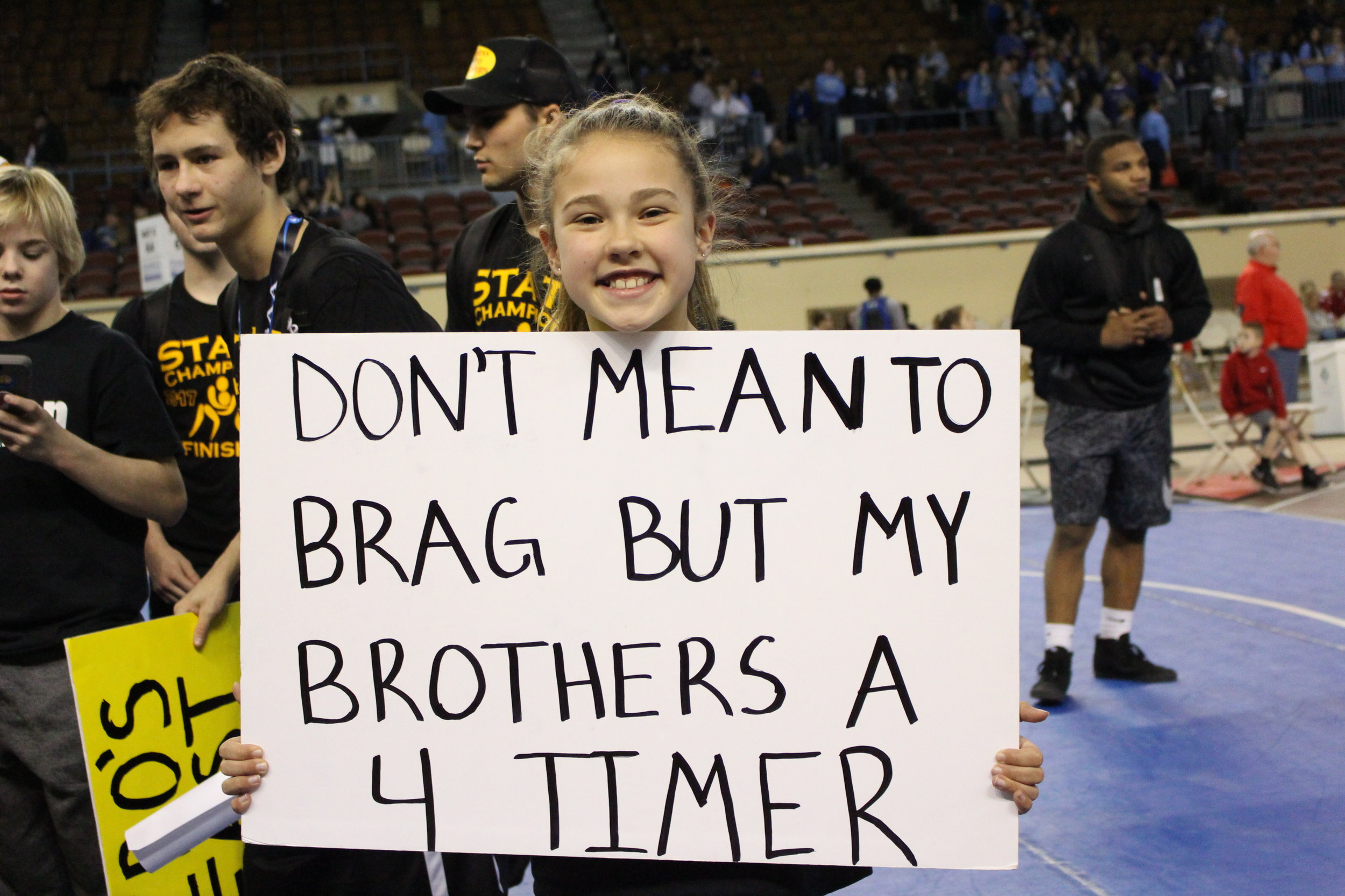 Dacee Smith holds a sign bragging on her brother, Daton.