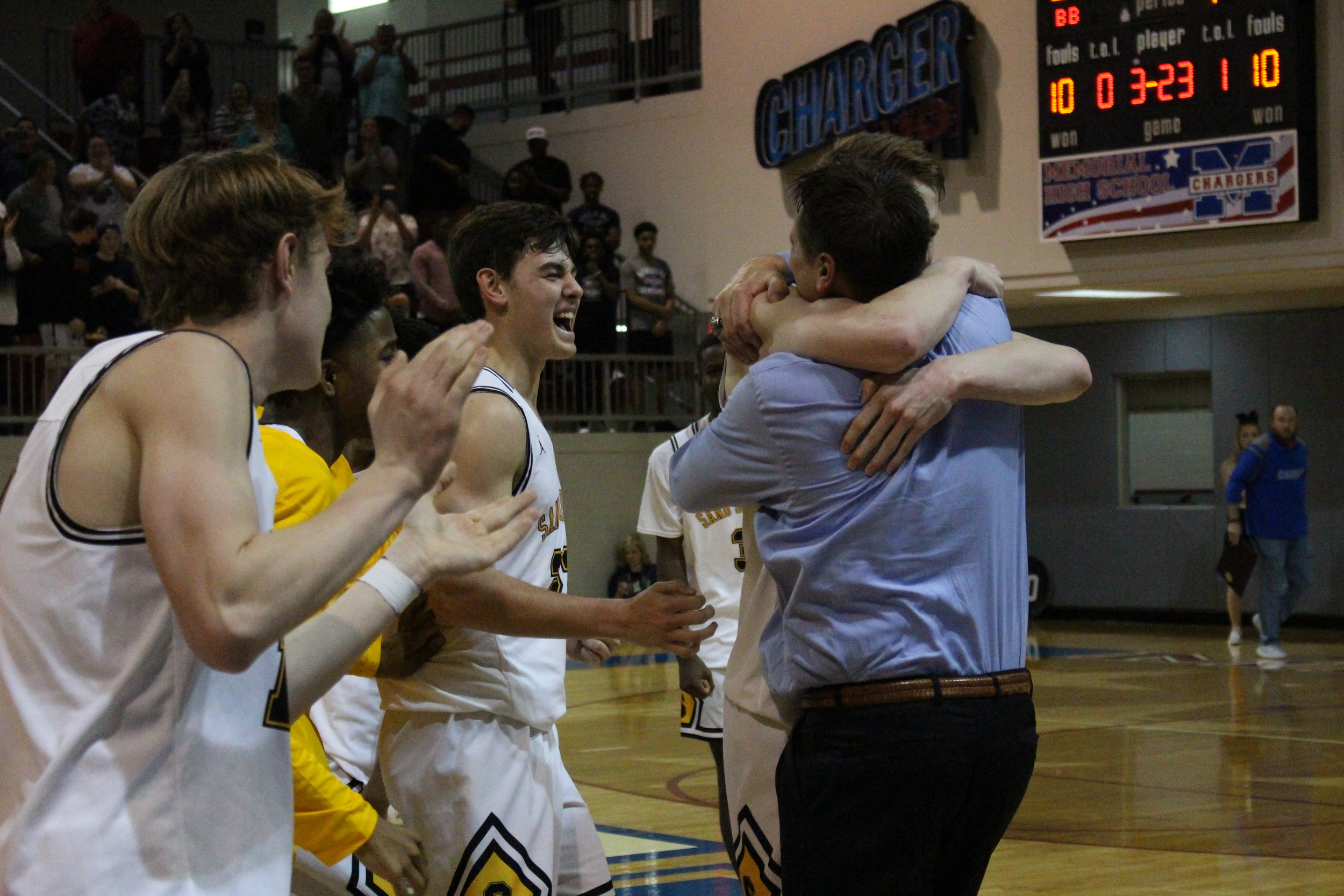 Cale, Colt, and Eric Savage celebrate after qualifying for the Sandites' first State Tournament appearance in half a century. (Photo: Morgan Miller).