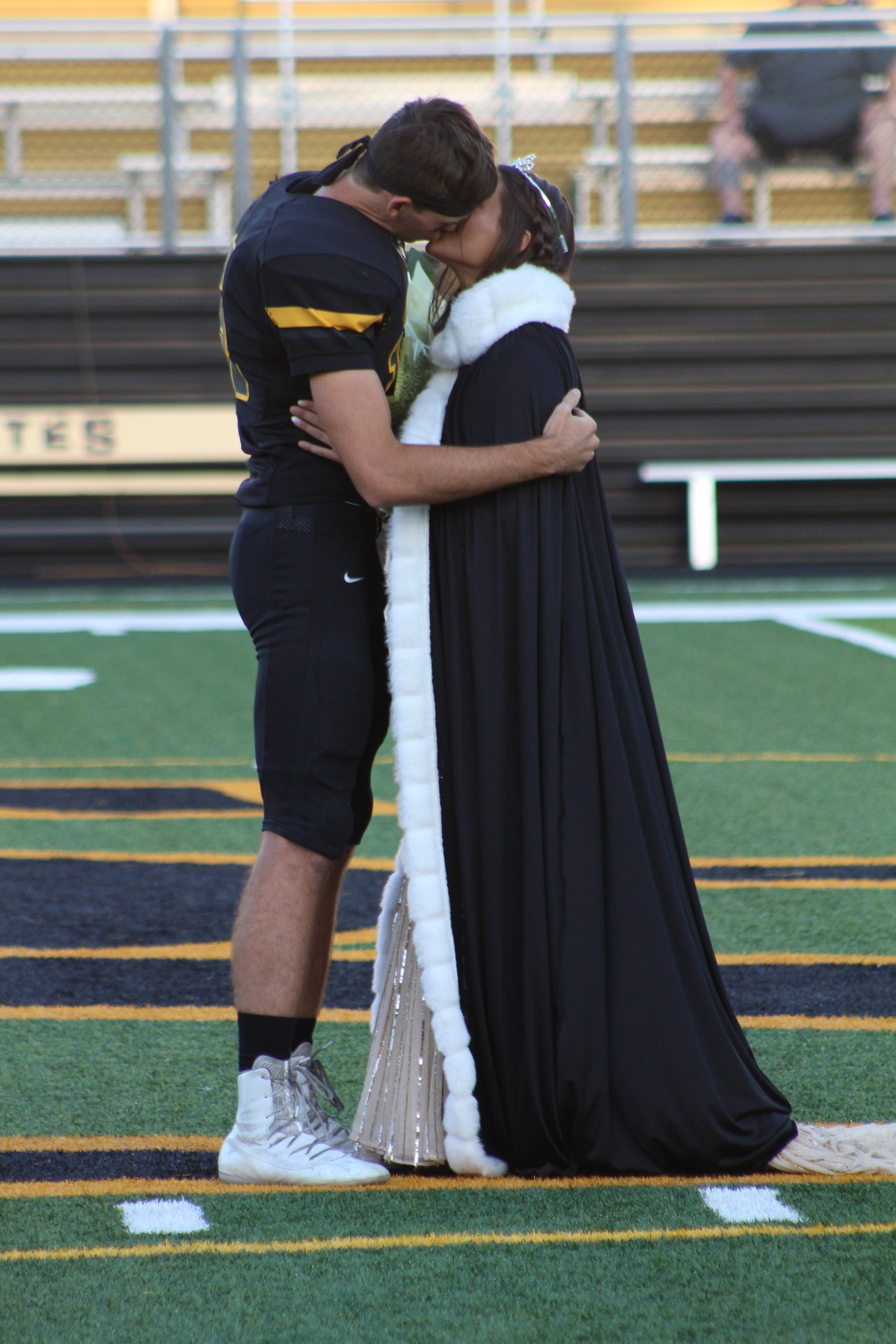 Kissing Captain Jerret Haley crowns and kisses Homecoming Queen Raegan Foster.