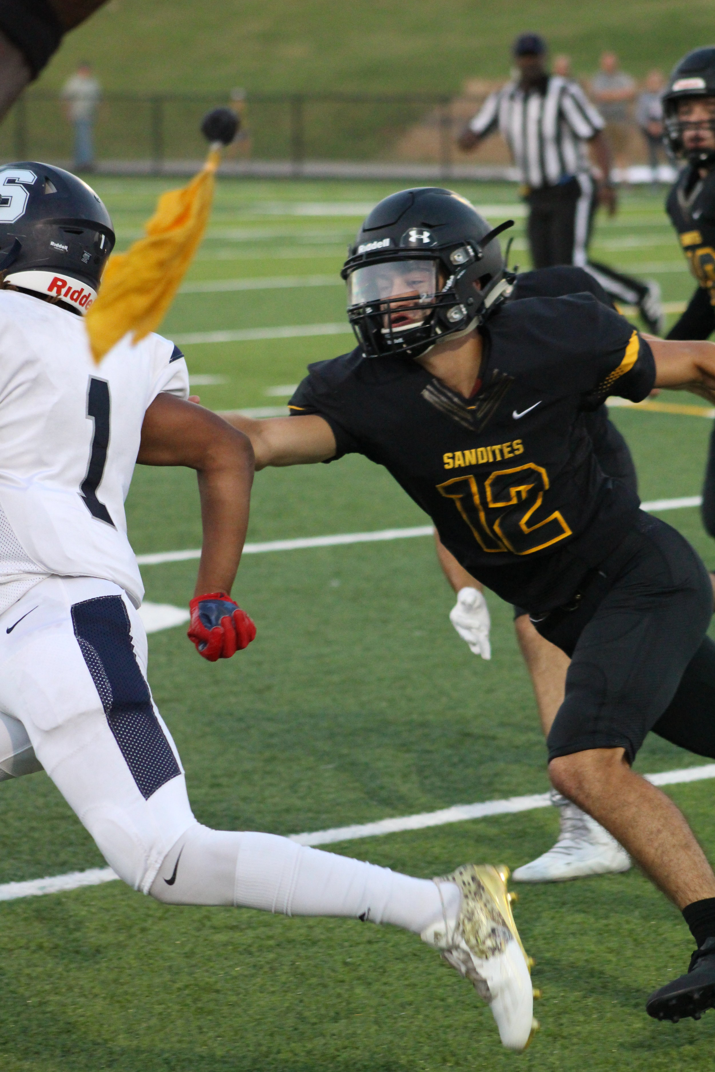 """Flags fly as Bryson Chase shoots for a tackle on Demetress Beavers. The 5'11"""" junior defensive back accounted for three pass break-ups against Shawnee."""