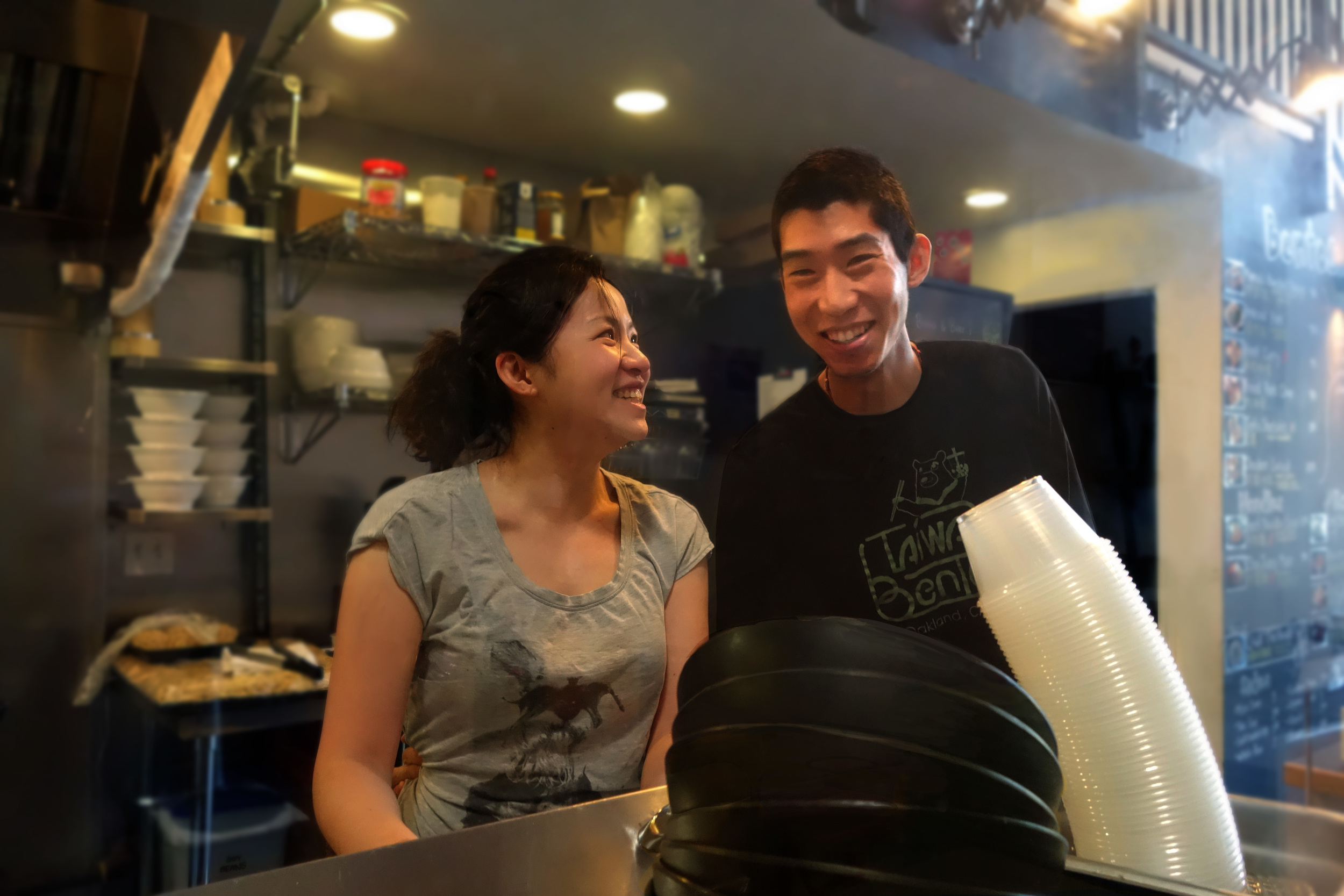 Stacy Tang (Left) and her husband, Willy Wang (Right). These owners of  Taiwan Bento  share a laugh during a busy Sunday morning. 2016.