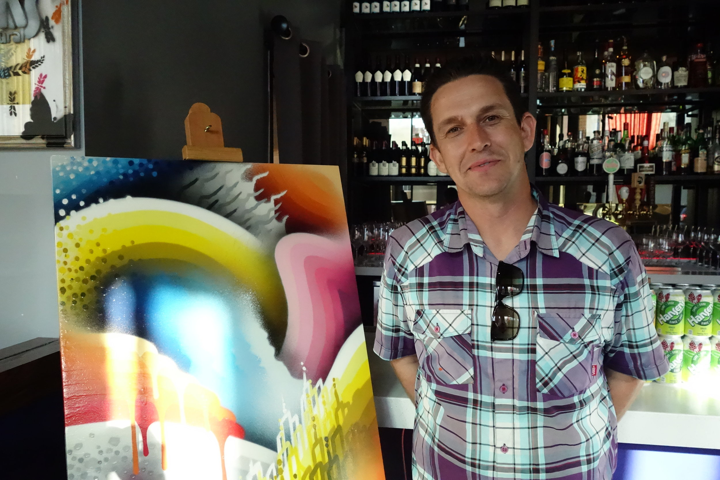 Local artist Ricky Watts poses in front of his artwork at Rooh SF in SoMa.