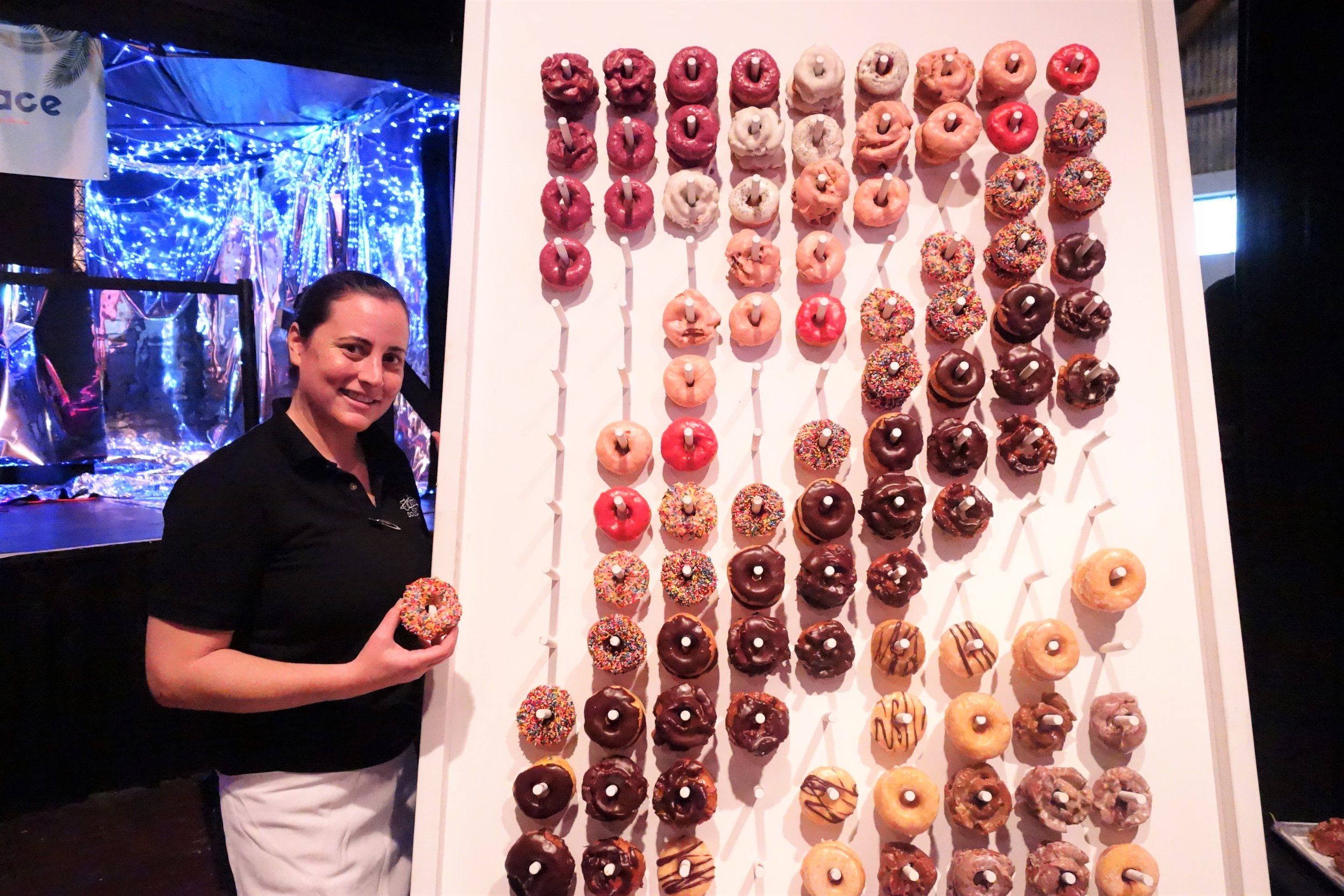 """Kristen from Johnny Doughnuts holds a """"Sprinkly Guys"""" Doughnut in front of their epic 10-foot doughnut wall at Sweet Spot Fest 2019"""