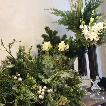 A beautiful mix of evergreens, silver brunia, white calla lilies, dendrobium orchids, and dogwood branches.