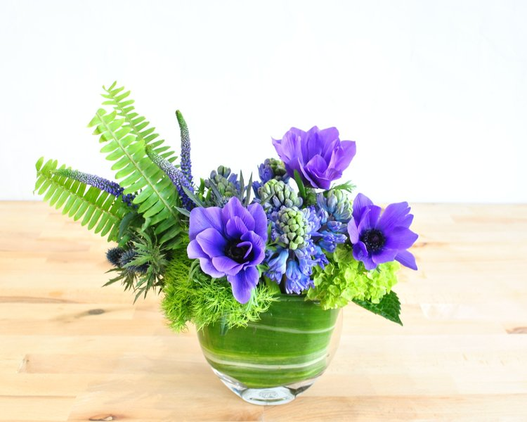 Cool, crisp and refreshing blues and purples pop against bitter greens. Fragrant hyacinth, anemones, veronica and hydrangea are accented with textural thistle and soft ferns, gathered together into a petite envelope vase.