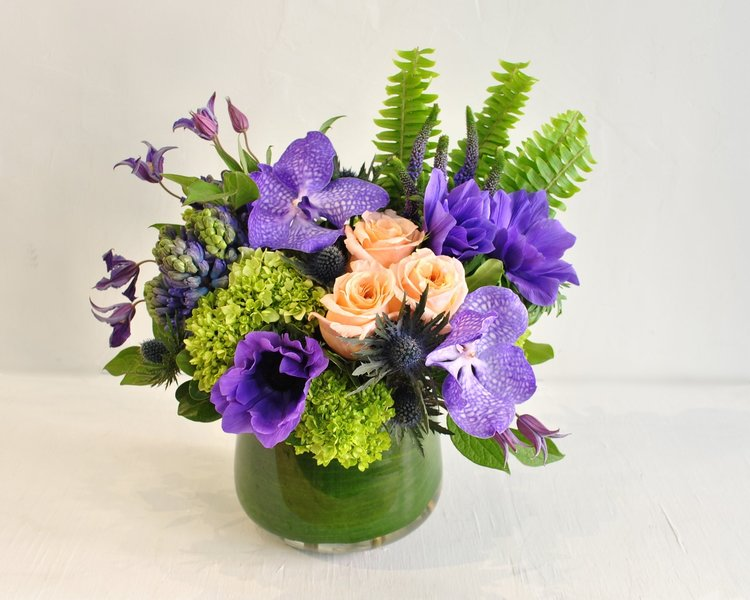 Crisp bright greens are the perfect setting for these rich purple hues. Fresh spring shades of anemones, hyacinth, clematis, veronica, shimmer roses and stunning vanda orchid blossoms are curated beside hydranges, soft fens and fun thistle, all together in a large rounded glass vase.