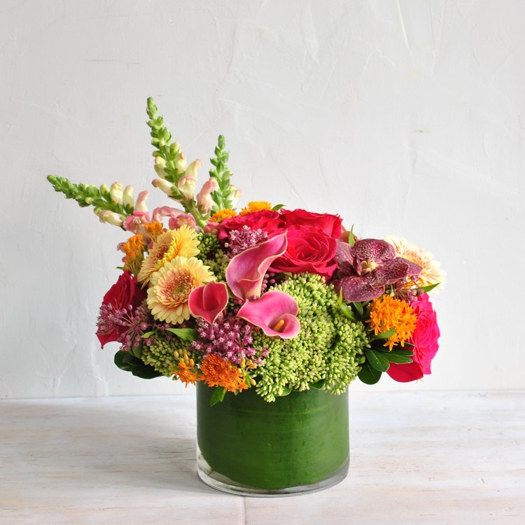 Monarch Bright, colorful tones of late summer combine into a glass cylinder vase. Hot pink roses, creamy gerbera daisies, pink calla lilies, astrantia and a pop of green sedum create a beautiful garden-inspired bouquet.
