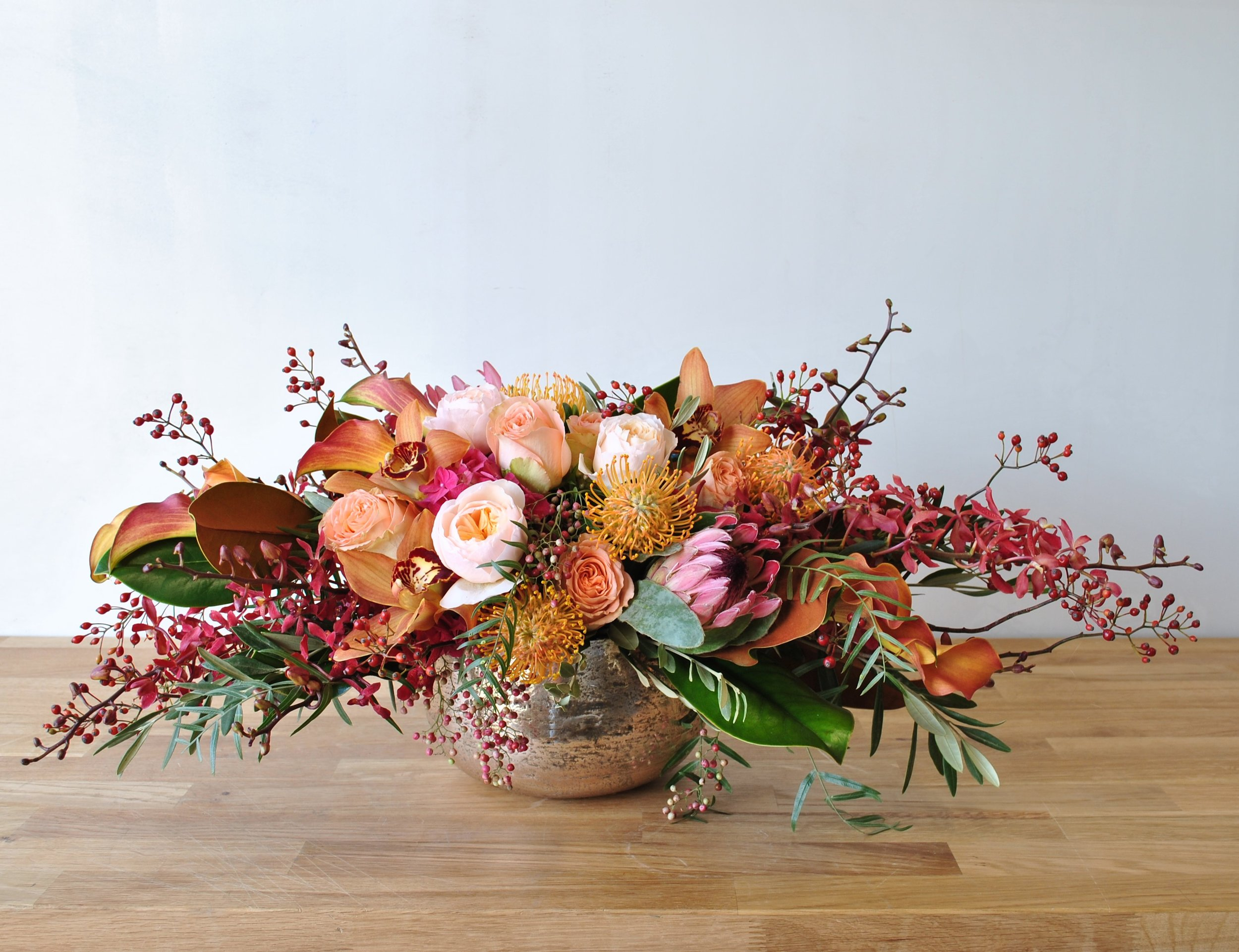 This stunning arrangement Pecan is a abundant autumnal masterpiece designed in our subtle rose gold mercury glass Siren bowl, with an elongated oval shape perfect for a large dining table holiday centerpiece. Deep pink dutch hydrangea, Juliet garden roses, mango calla lilies, & two types of protea have great focal appeal when paired with highly textural james storeii orchids, rose hips, pepperberry and rich magnolia leaves.