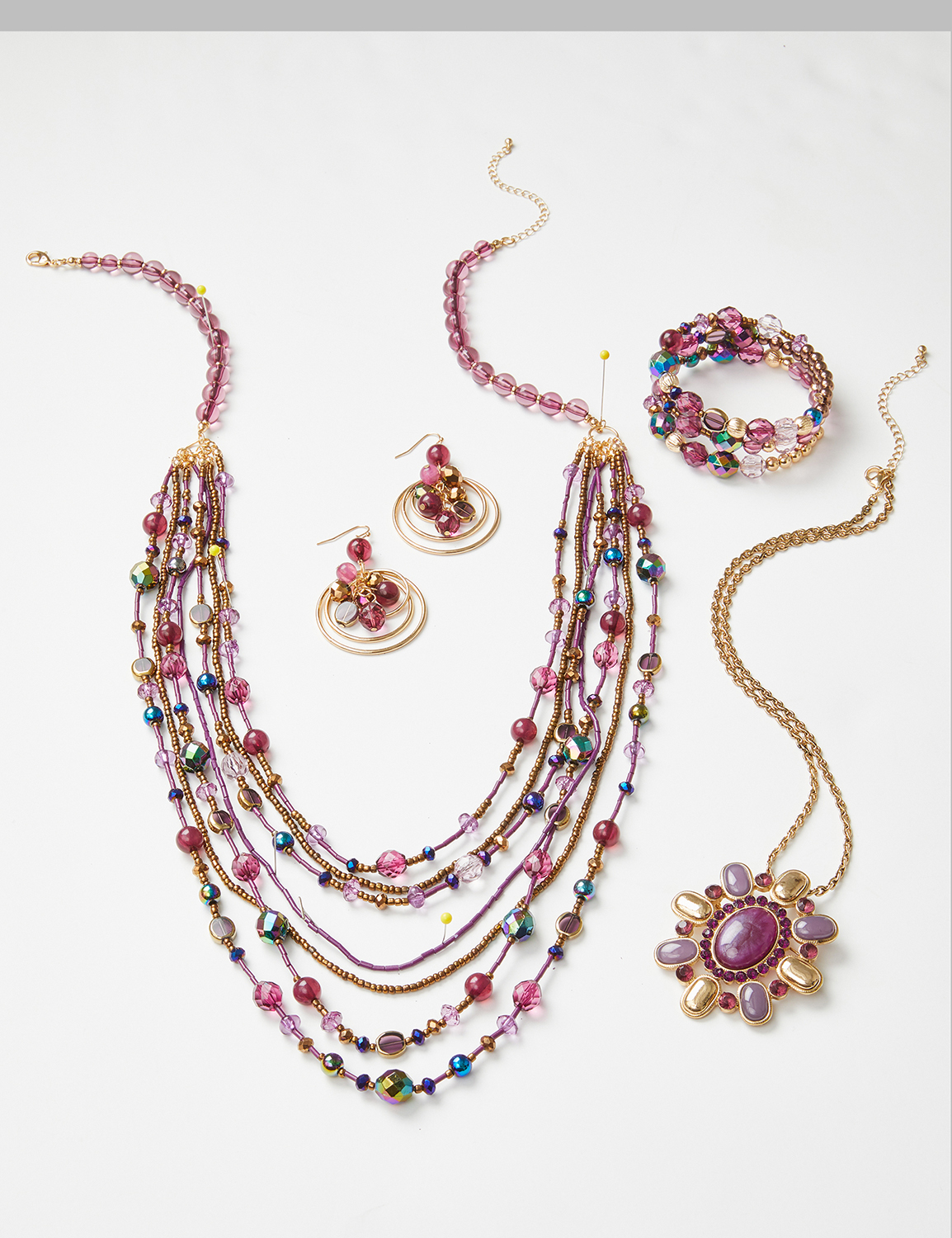 product laydown of multi-beaded necklace, earrings, and bracelet jewelry set