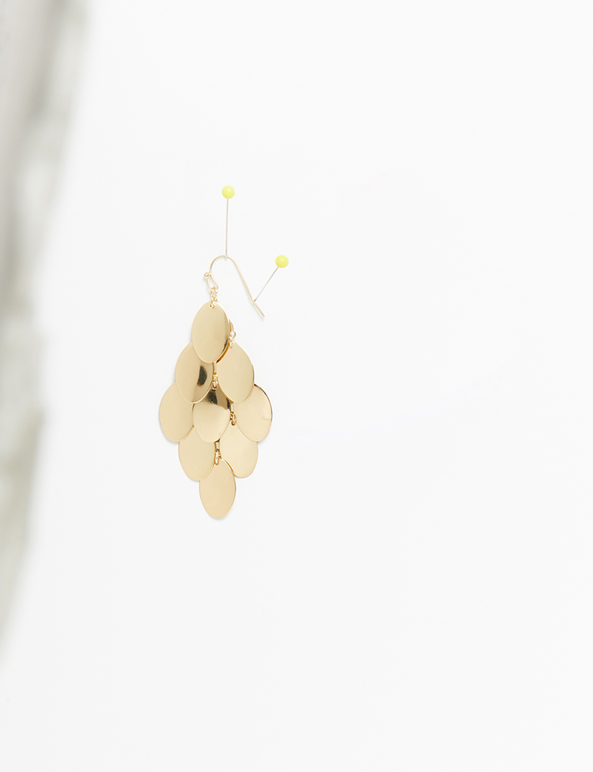 single gold disk chandelier earring on white background.