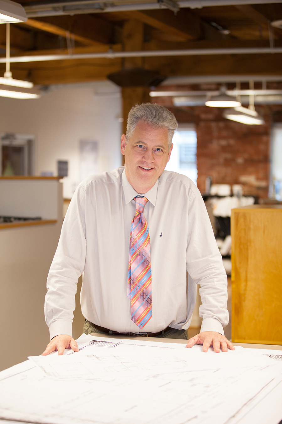 headshot of professional man in office with architectural plans