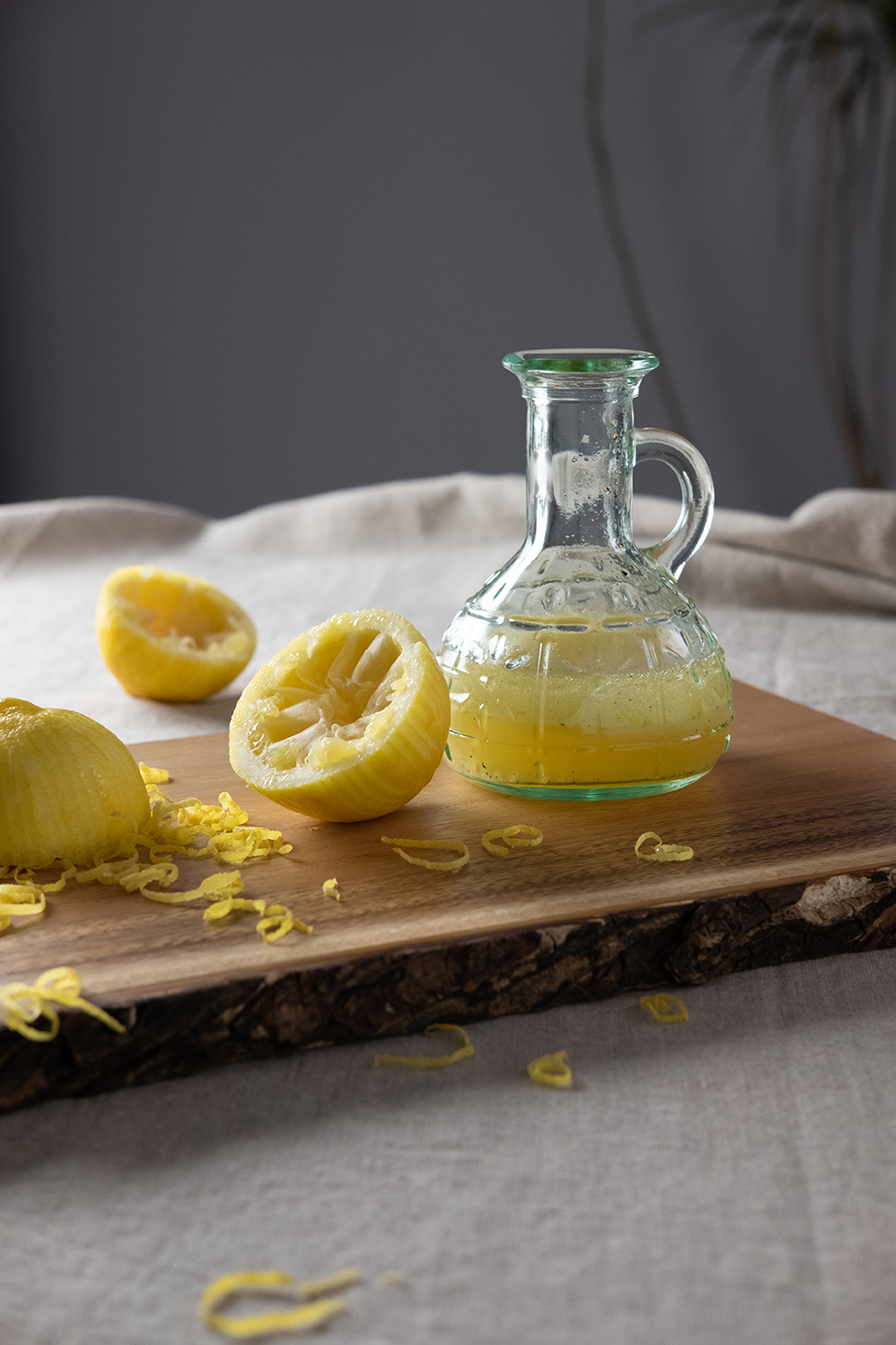 small glass pitcher of lemon dressing and lemons on wooden plank