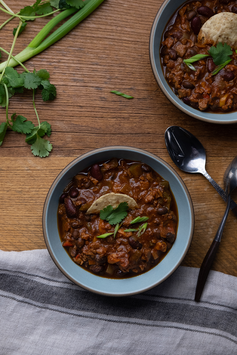 bowls of vegetarian chili on a rustic wooden table