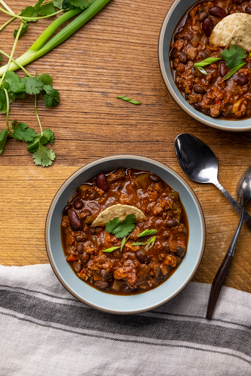retouched bowls of vegetarian chili on a rustic wooden table