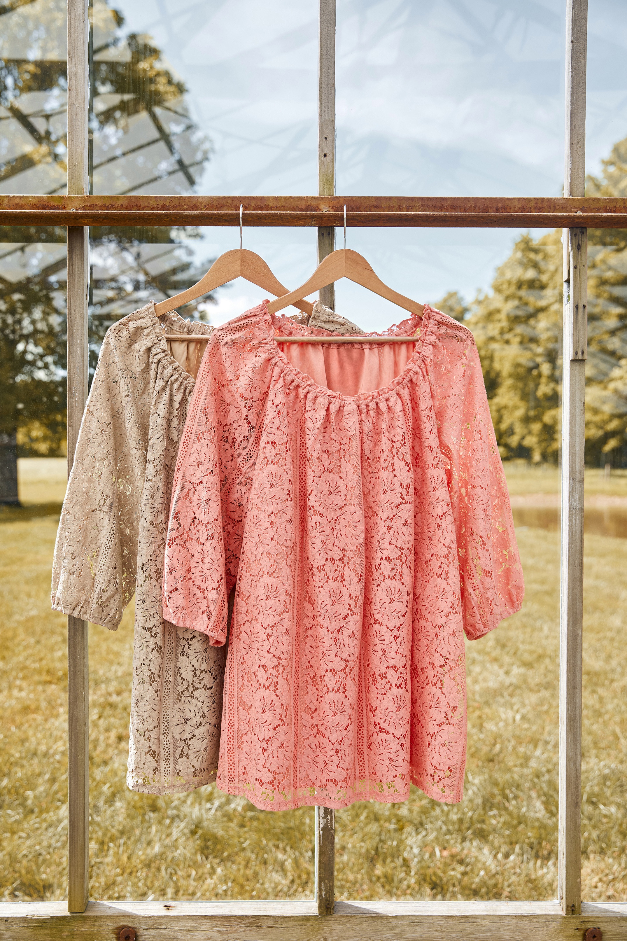 retouched brown and pink lace shirts hanging in window frame on sunny autumn day