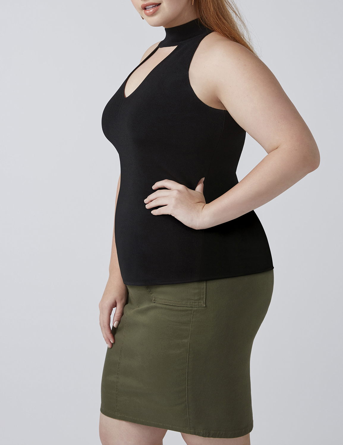 retouched fashion model in black tank top and military green skirt posing with hand on hip