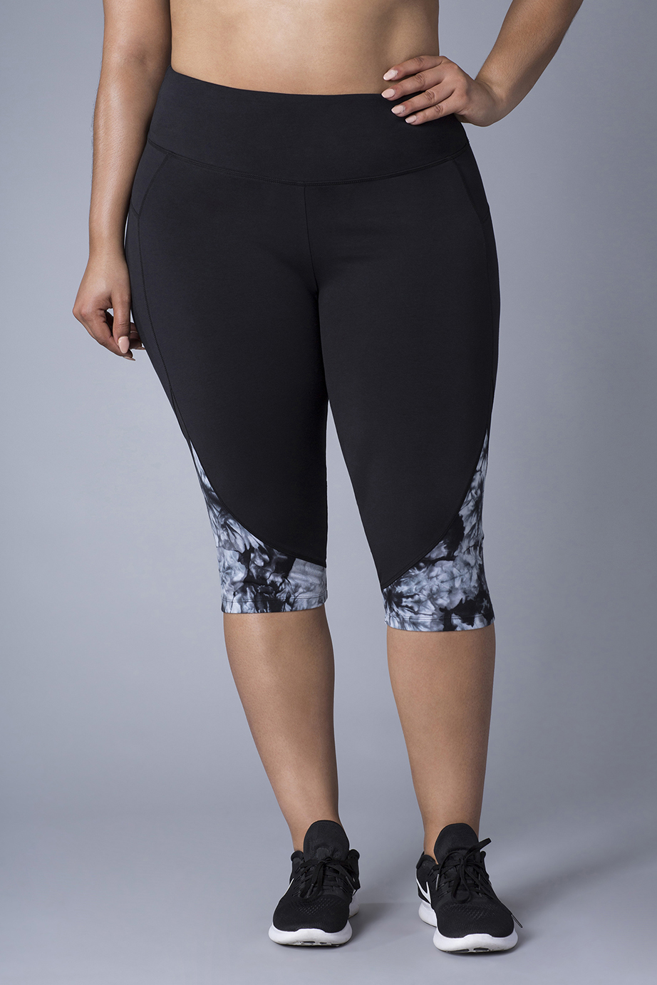 retouched woman, hand on hip, wearing black athletic capri leggings