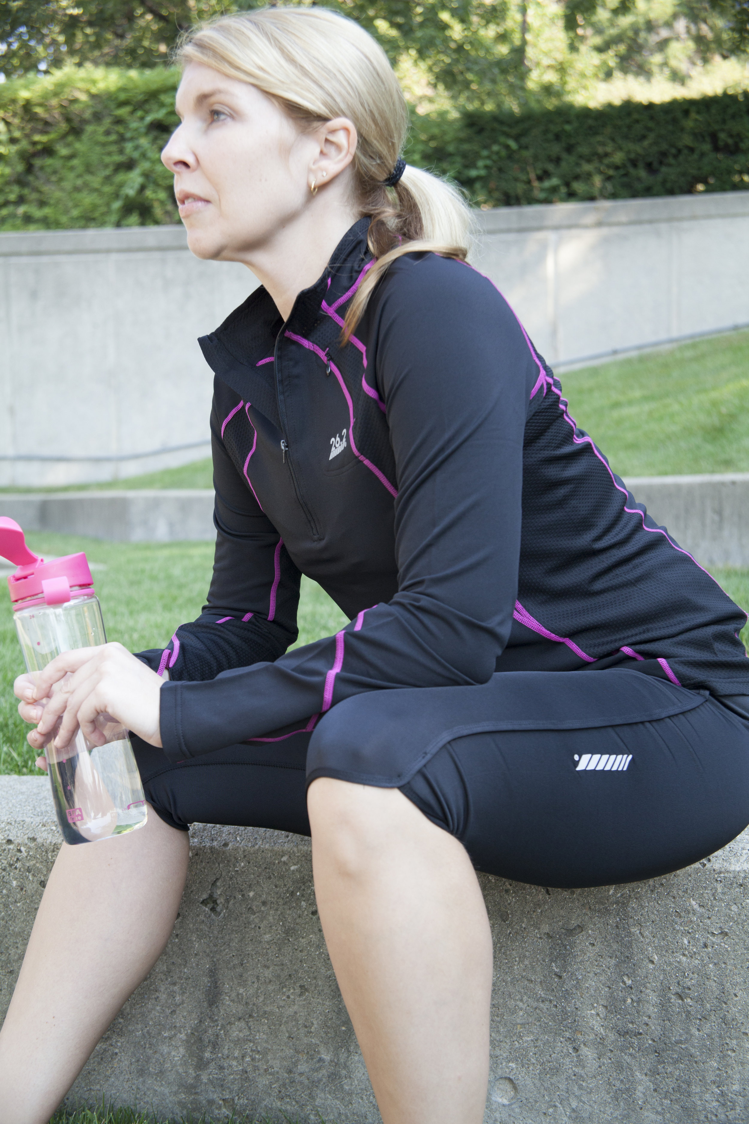 athletic woman sitting in the park holding a water bottle