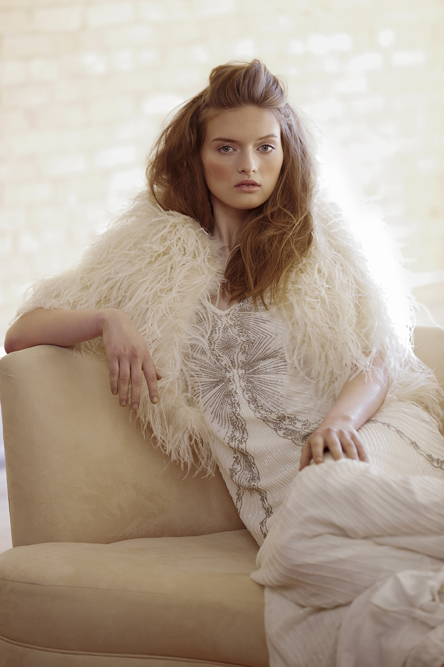 retouched bride resting on sofa in feathered jacket